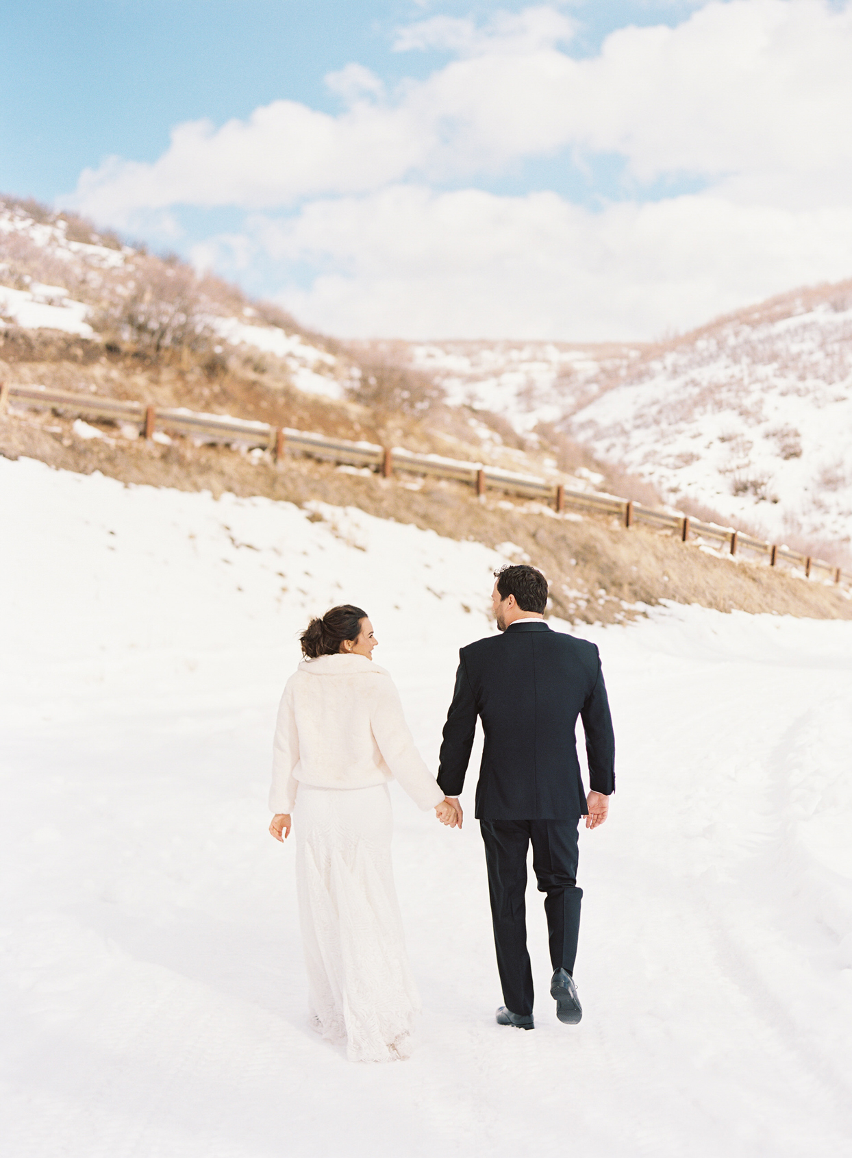 bride and groom hold hands walking away outside in the snow
