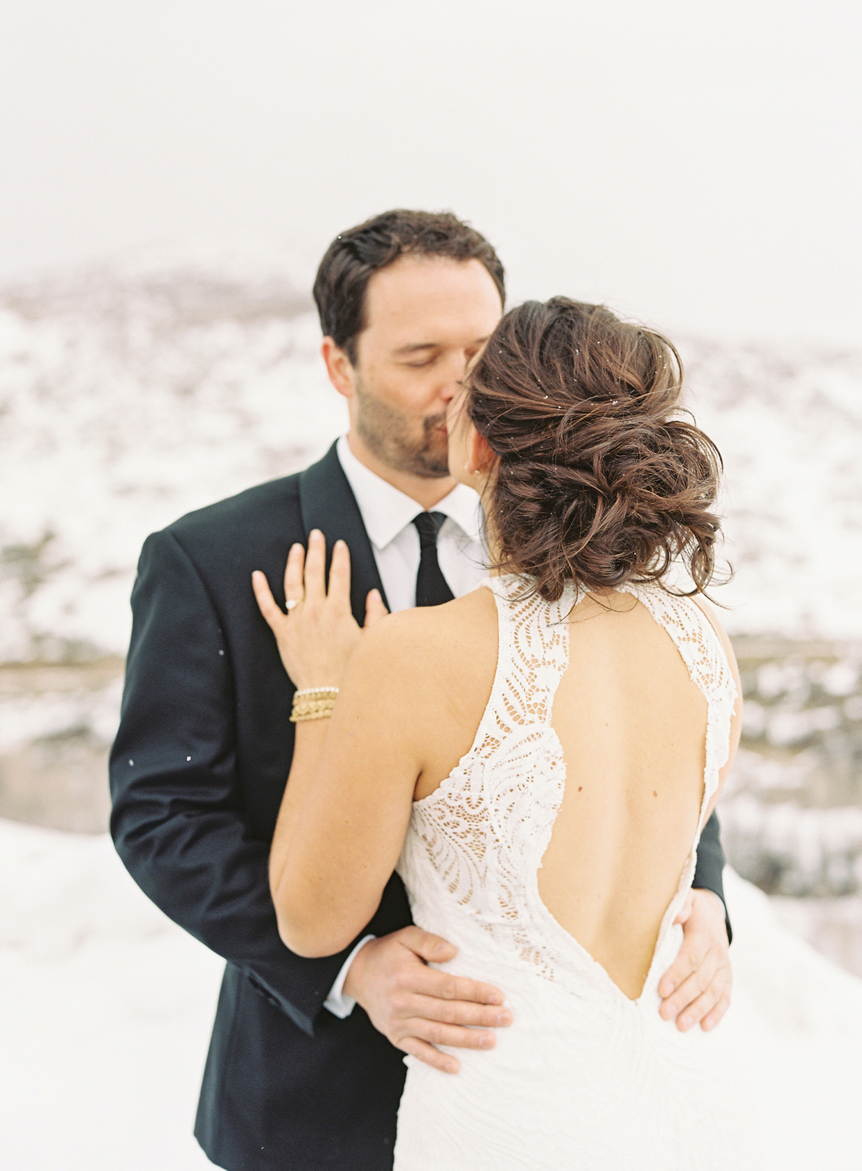 bride and groom hug while sharing a kiss outside in the snow