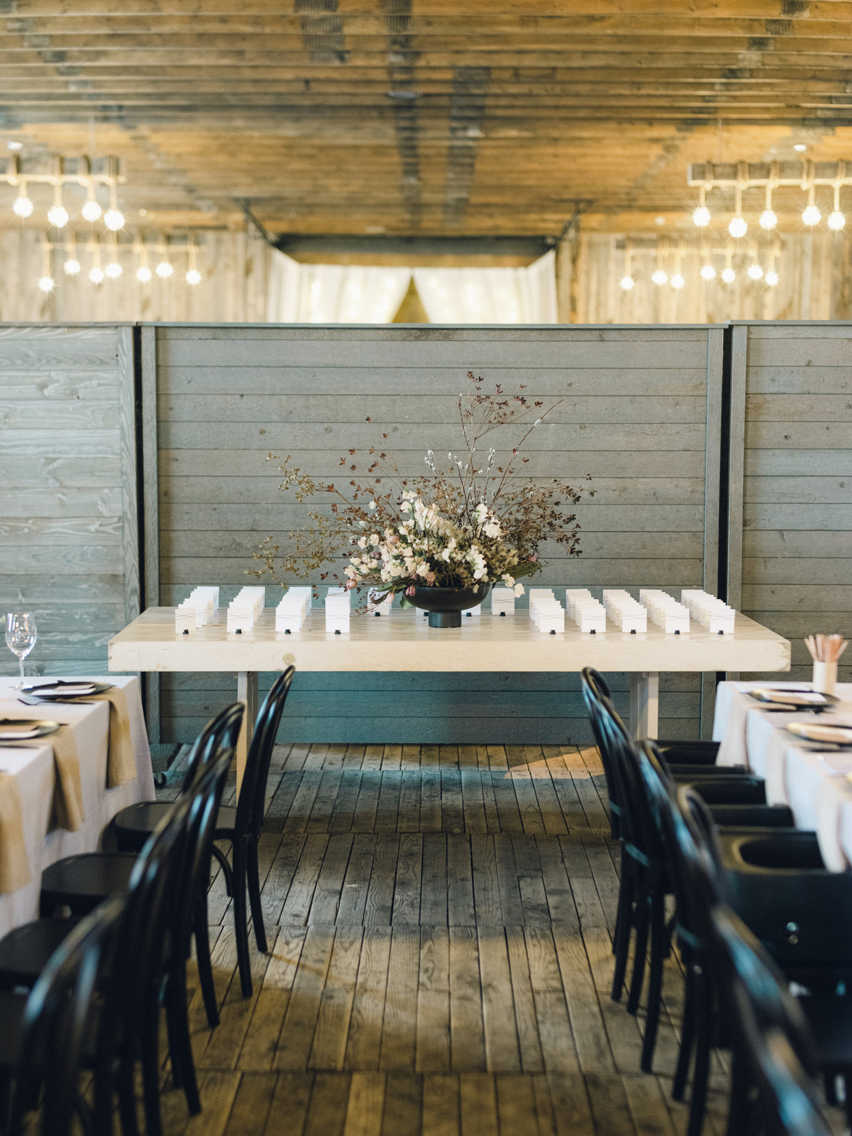 table with large floral centerpiece and white escort cards