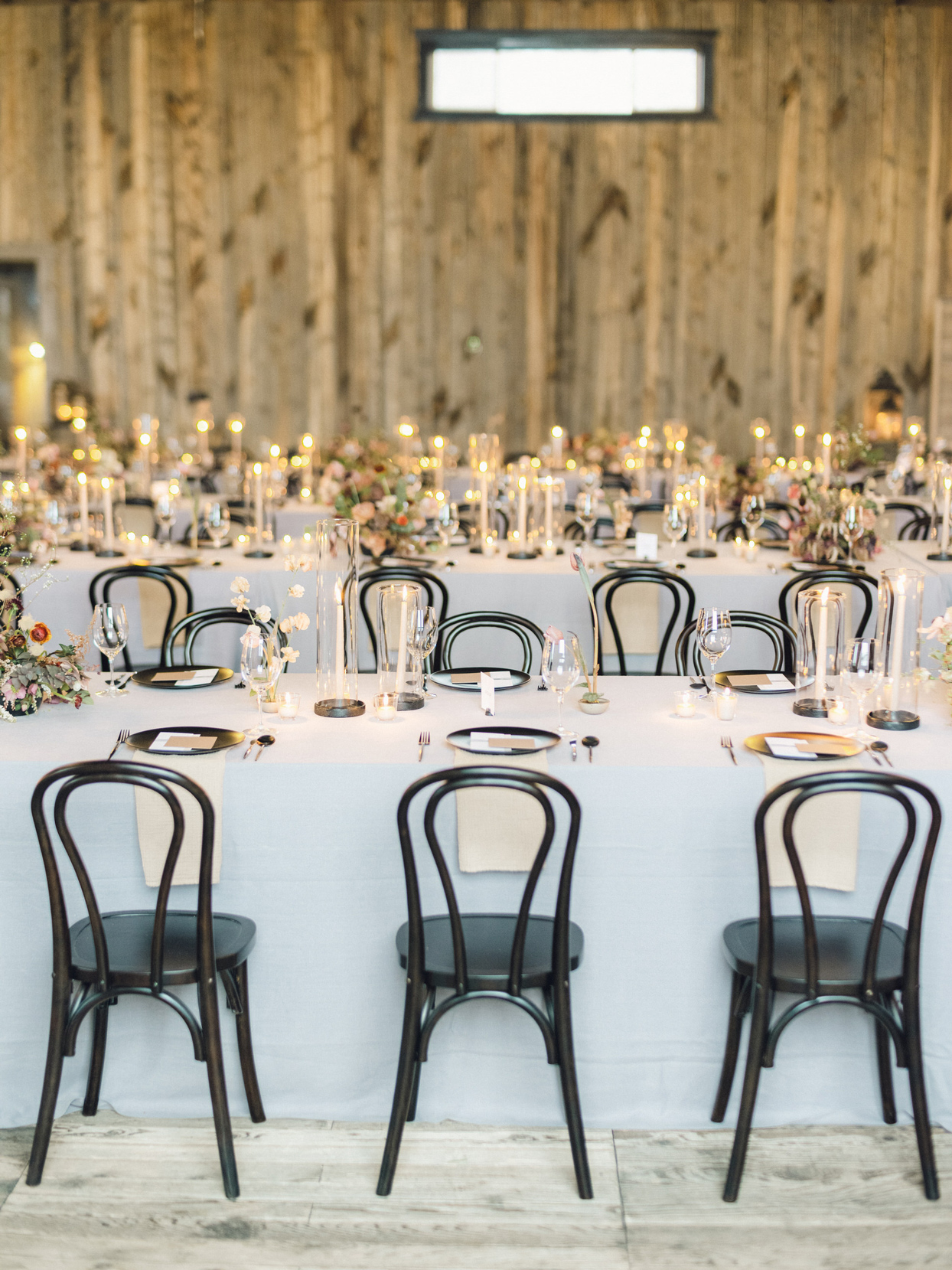 long white linen covered table with black chairs