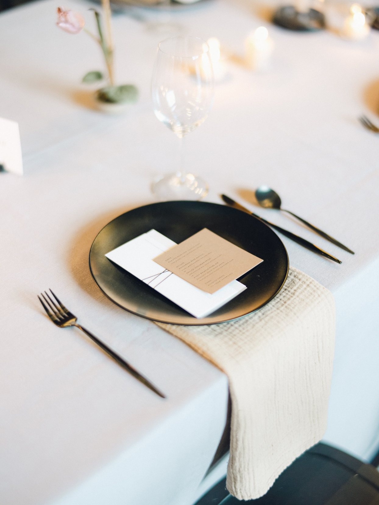 simplistic black place setting with tan linen and menu card