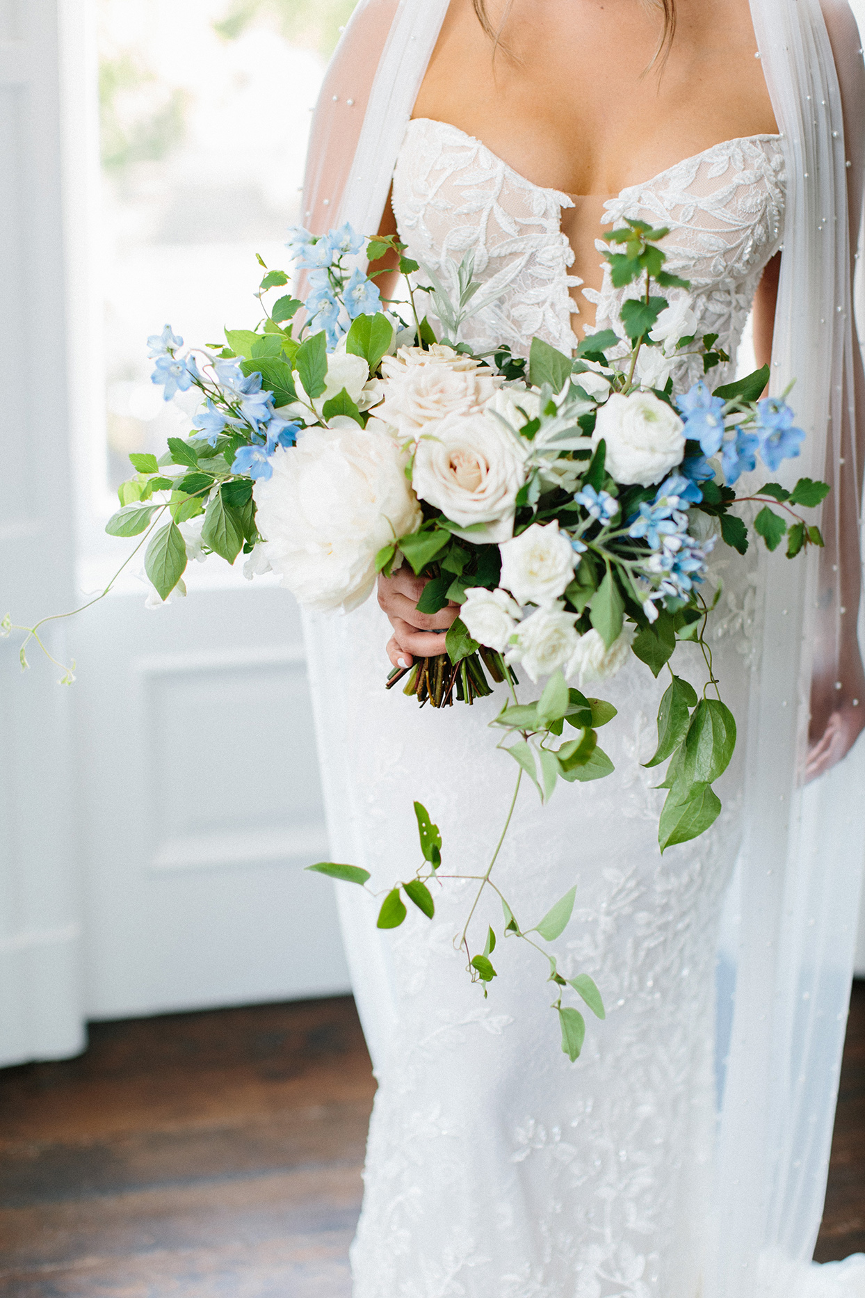 bride holding white and blue floral wedding bouquet with greenery