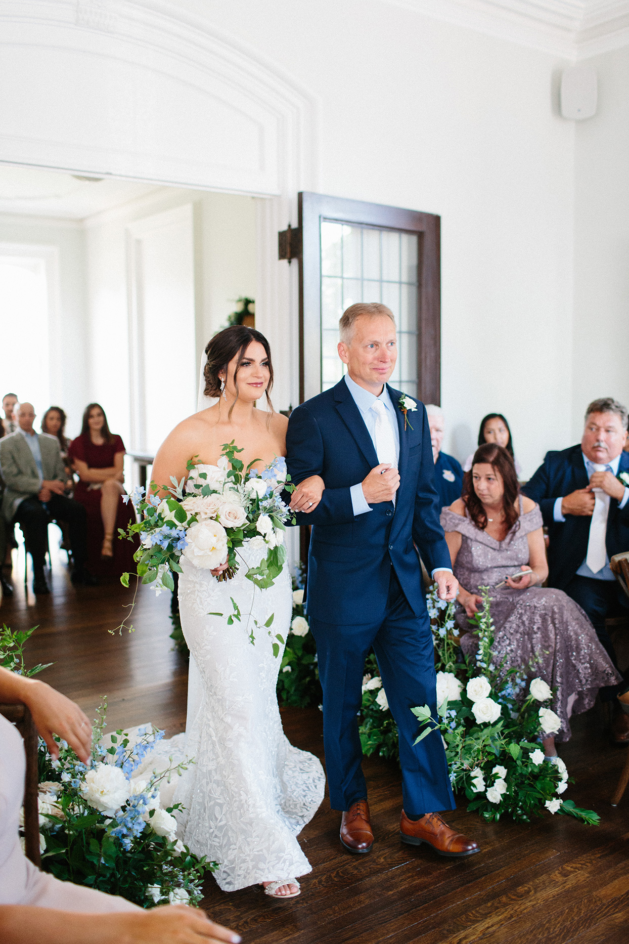bride with father linking arms walking down processional aisle