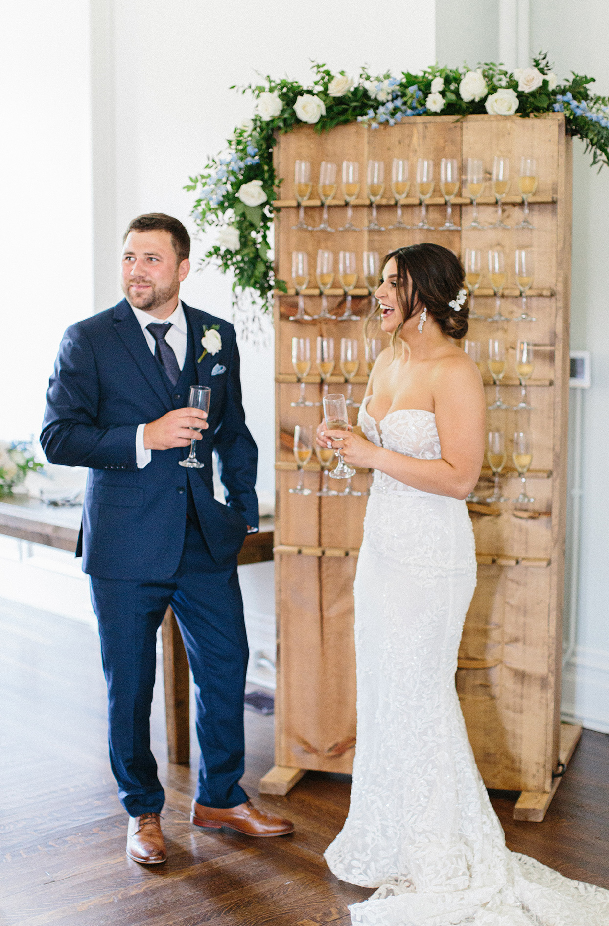 wedding couple standing next to small wall display of champagne