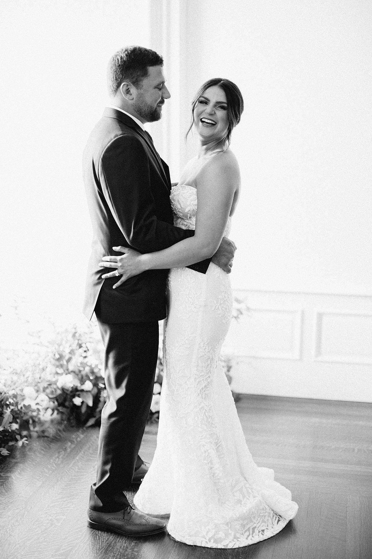 bride laughing while groom smiles at her during first dance
