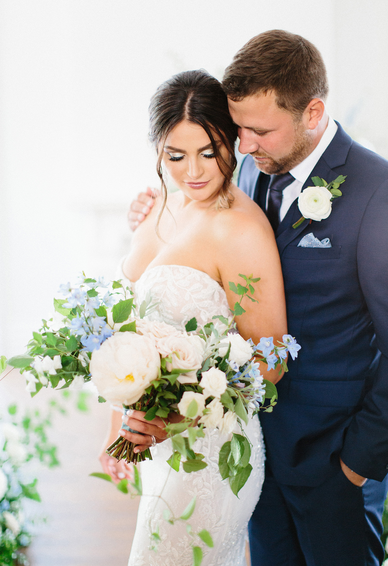 groom standing behind bride with hand on her shoulder as she leans back into him