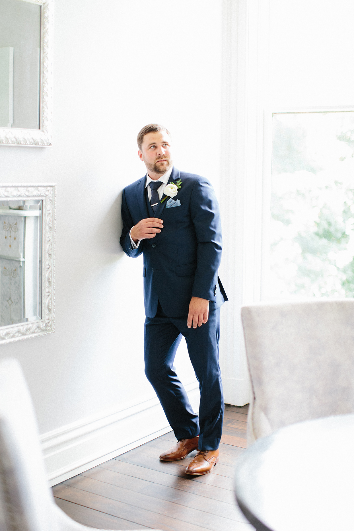 groom leaning against white wall in navy blue suit