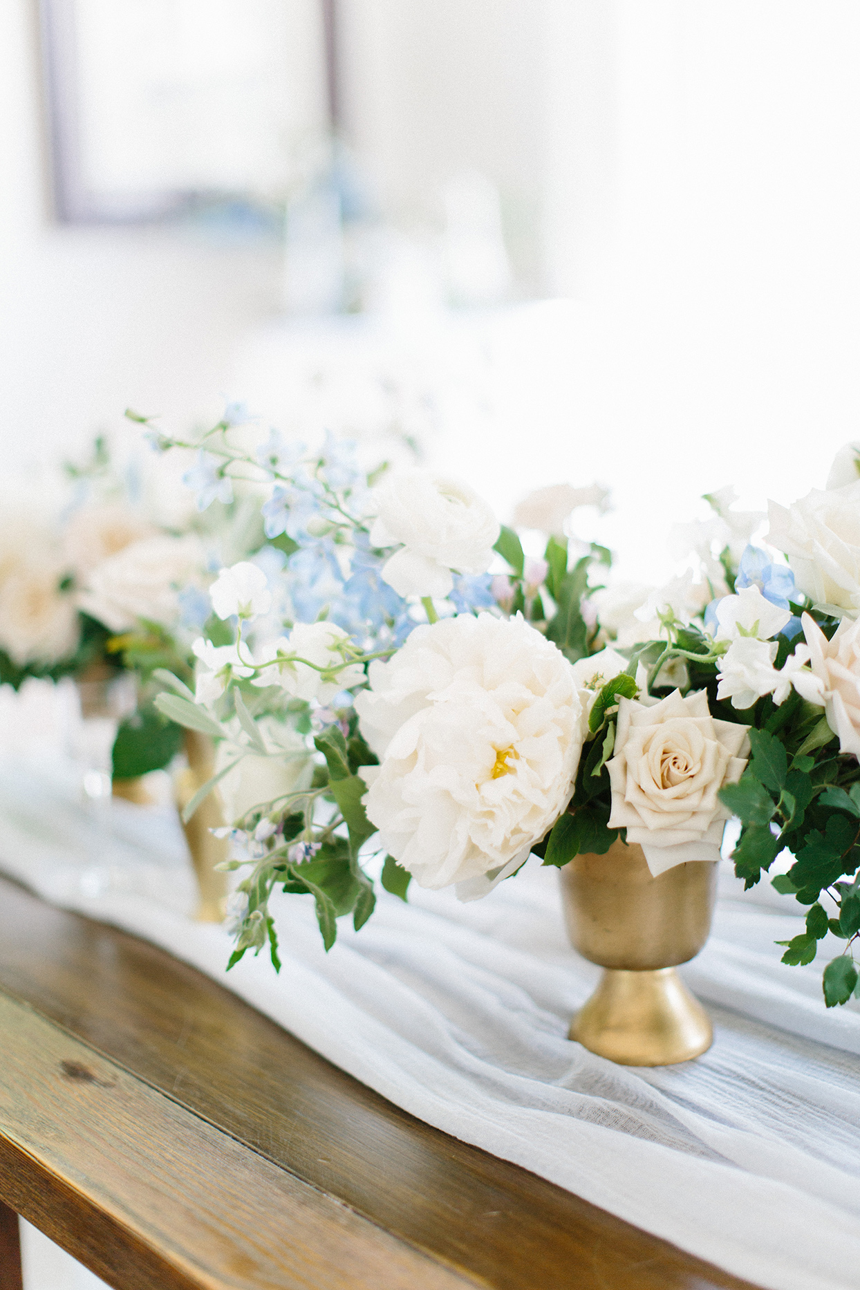gold vase filled with white and blue flowers and greenery