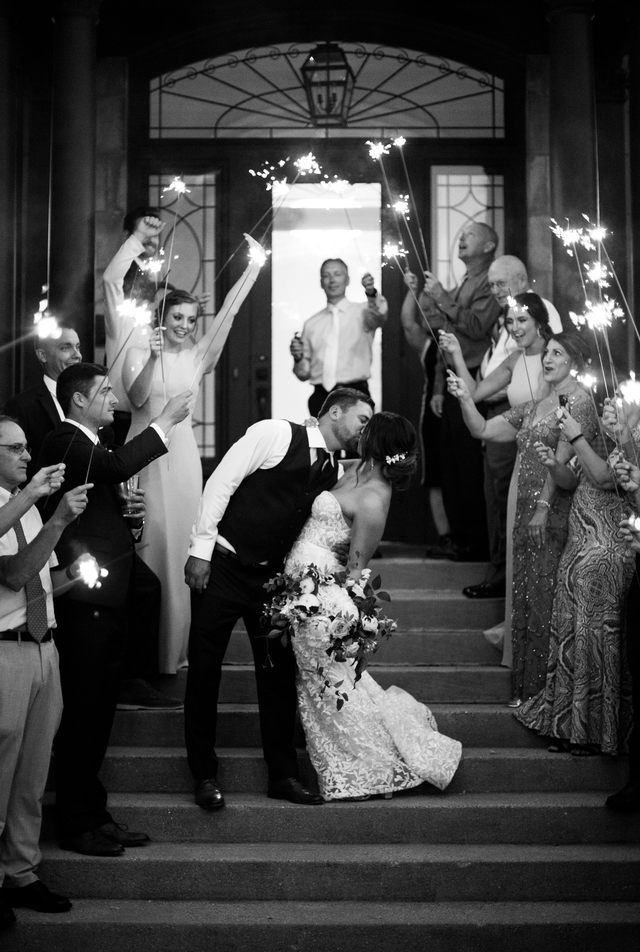 bride and groom kiss on stairway under sparklers held by guests