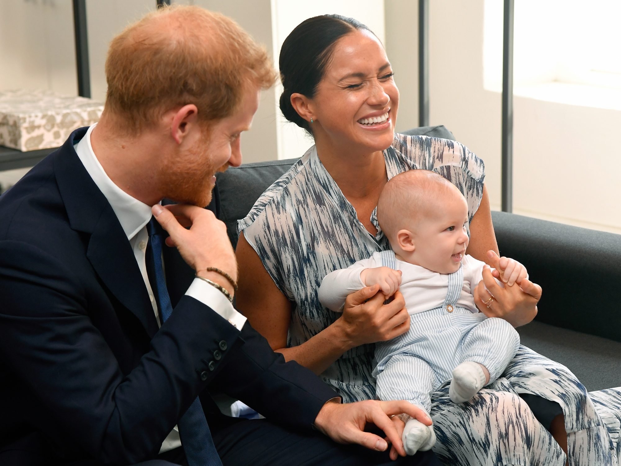 prince harry and meghan markle laughing while holding archie