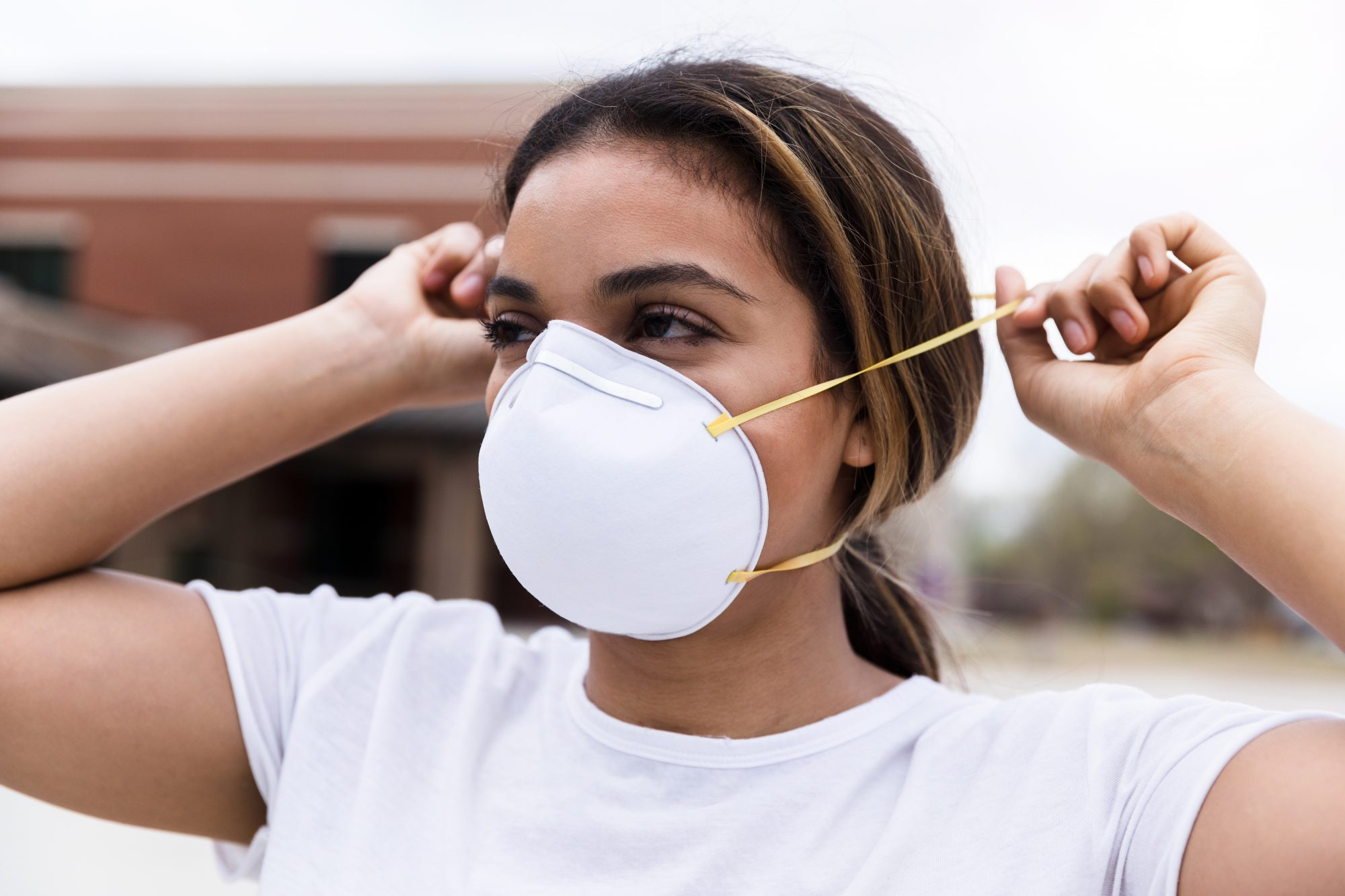 woman putting on N95 face mask