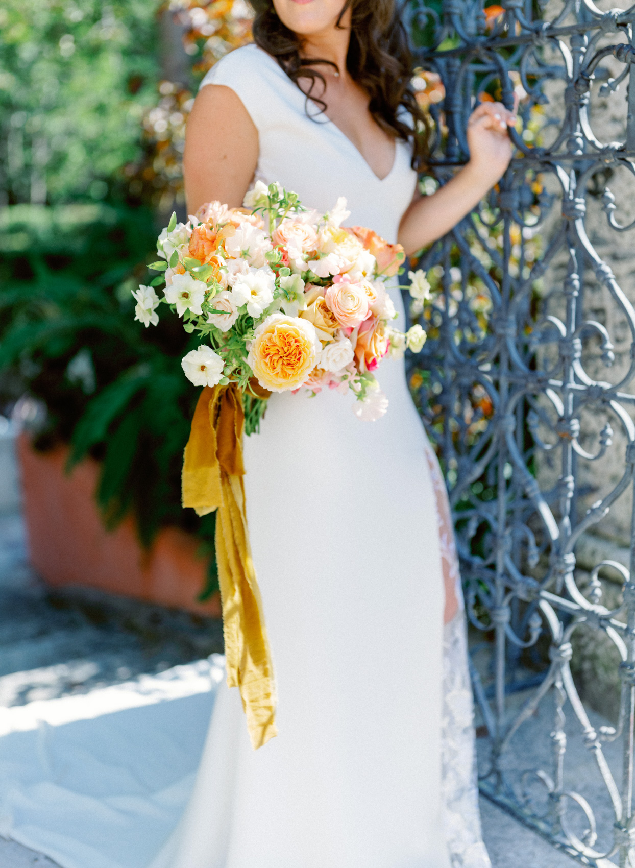 bride holding orange and pink wedding bouquet