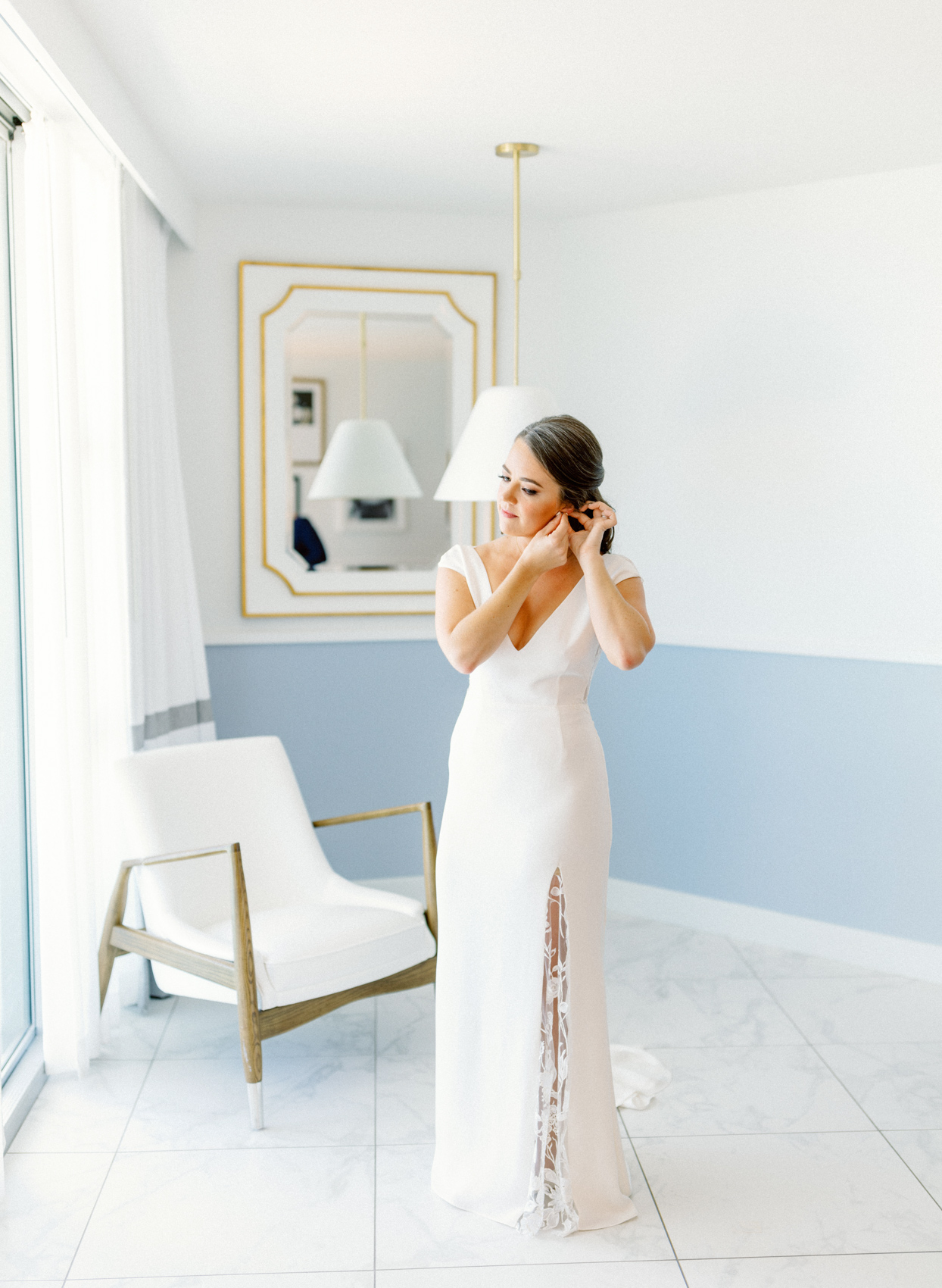 bride getting ready for wedding in white and blue brightly lit room