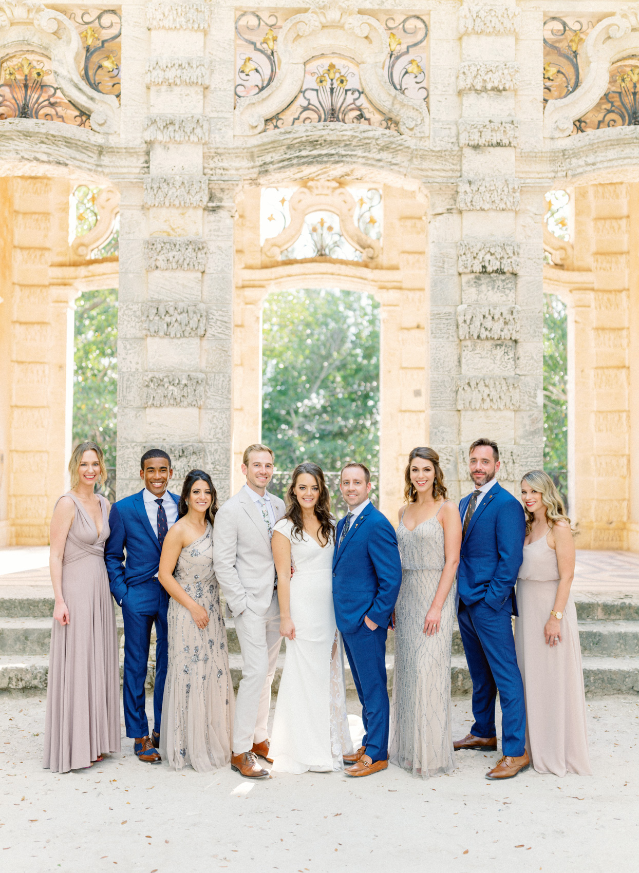 wedding party in blue and beige posing on stone steps