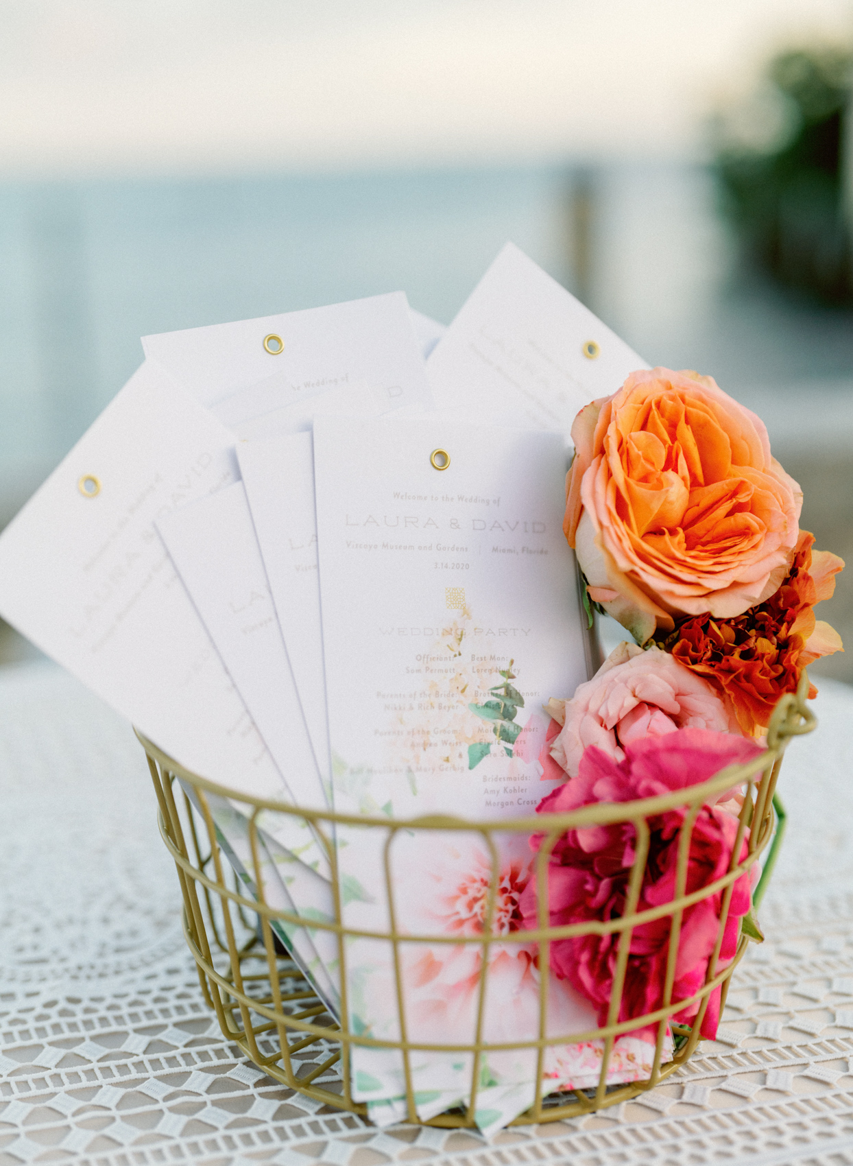 elegant white ceremony programs in gold basket with flowers