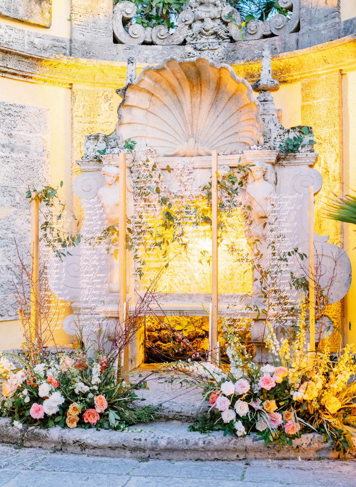 elegantly lit stone structure with clear seating chart and flowers