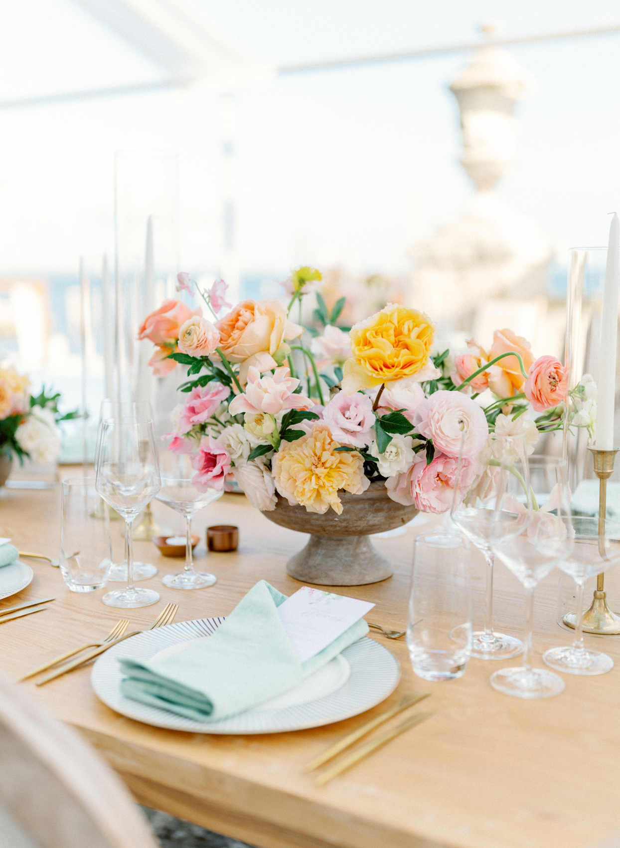 wooden table with pastel place setting and floral centerpiece