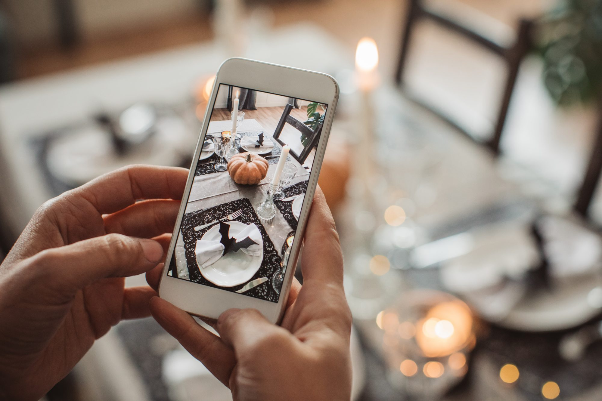 woman photographing table for a virtual Halloween party