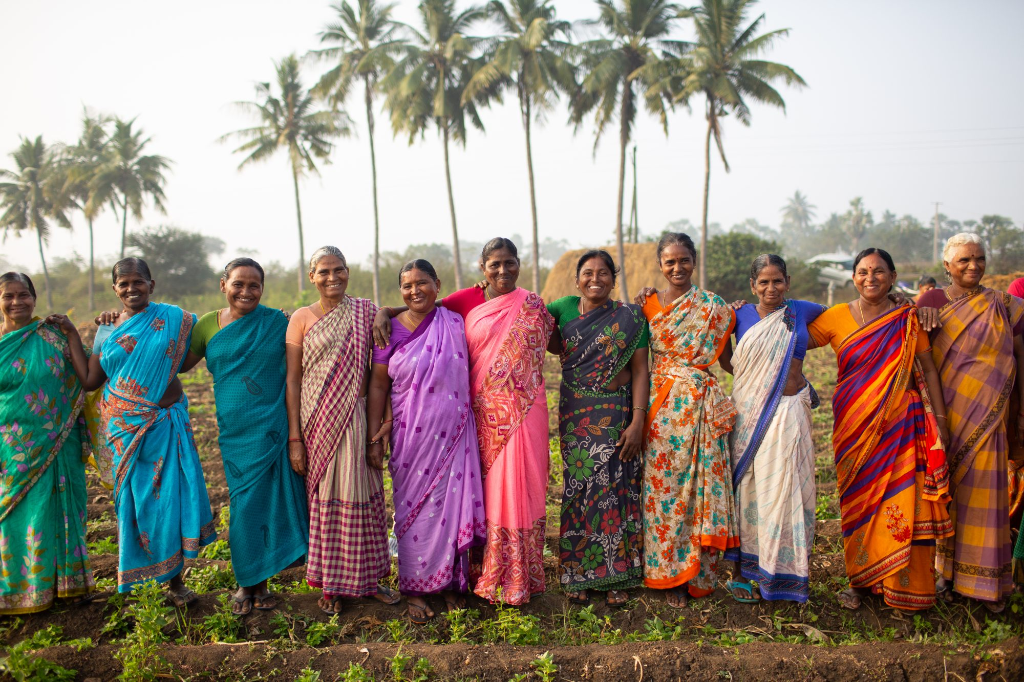 group of women spice farmers in colorful saris in a field in India