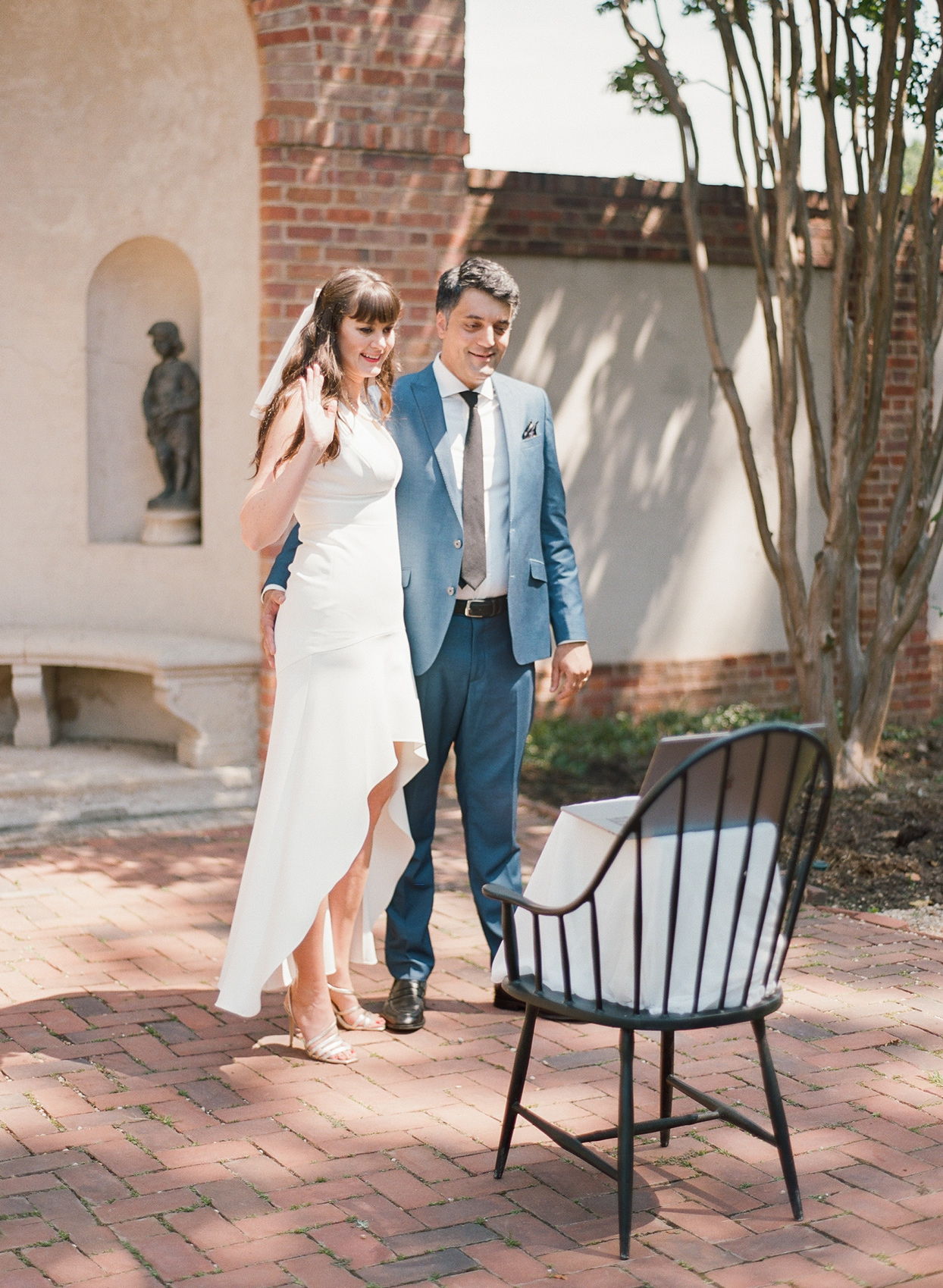bride and groom waving at laptop propped up on chair