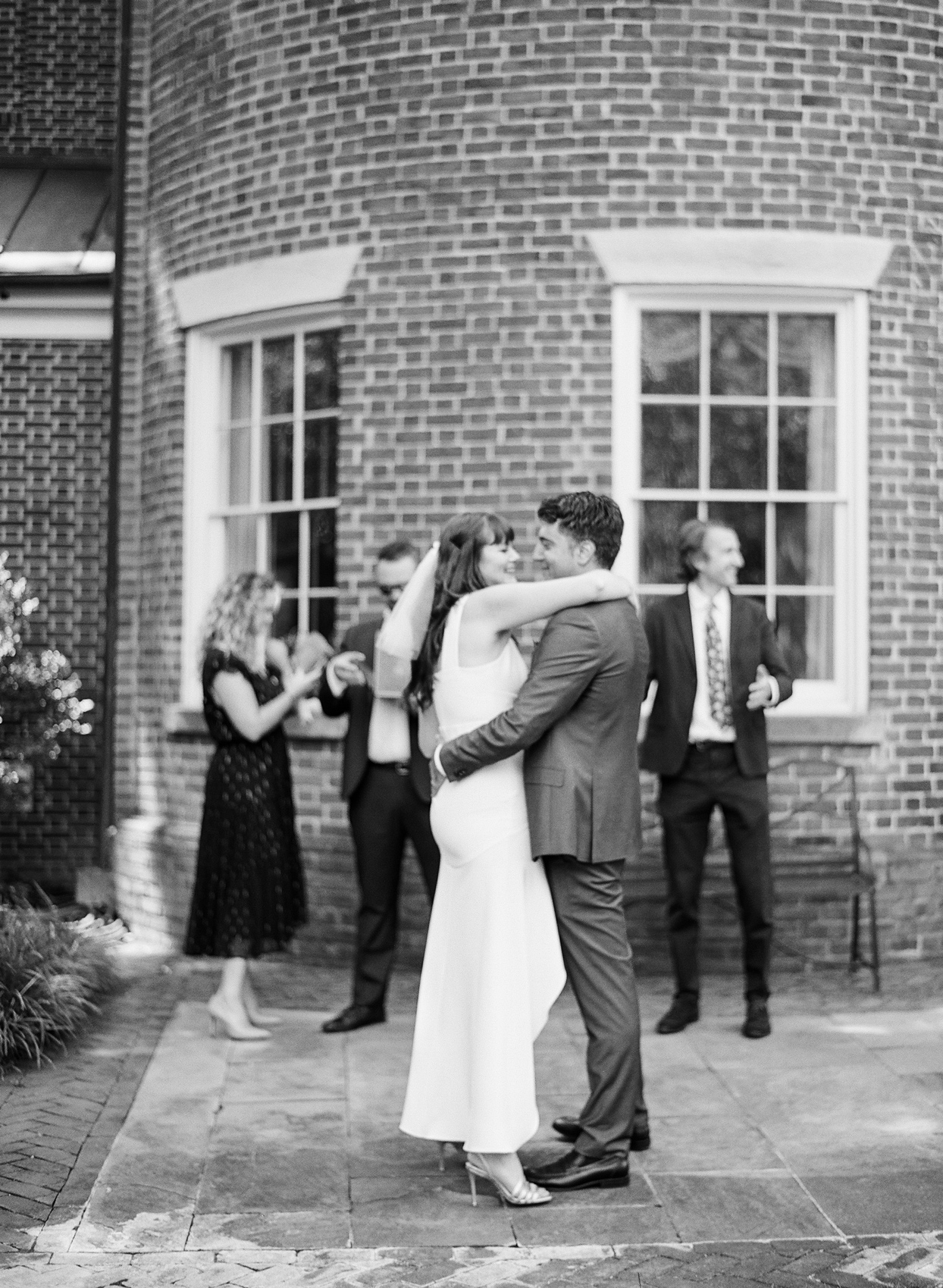bride and groom sharing first dance in courtyard