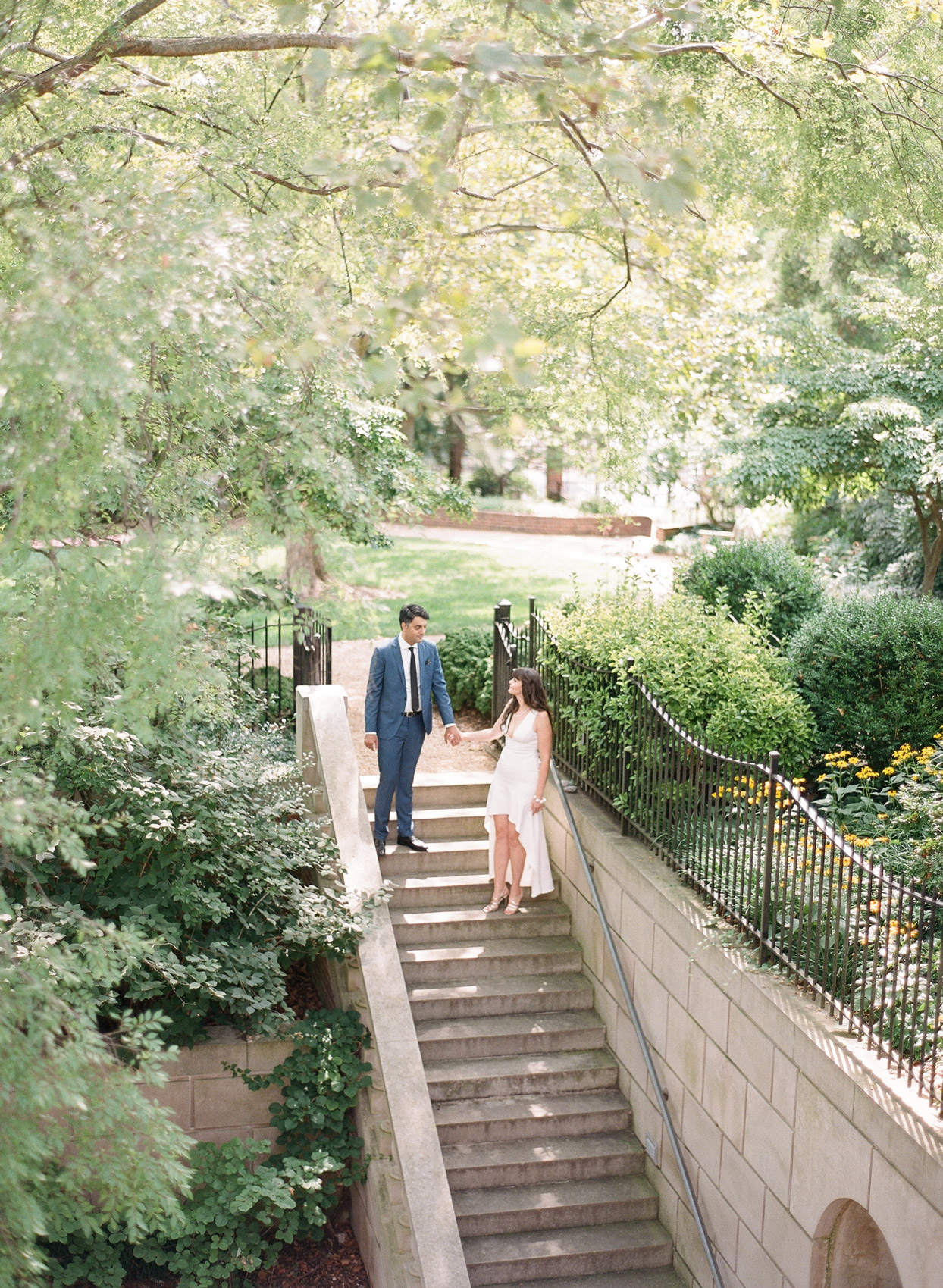 bride and groom holding hands descending staircase