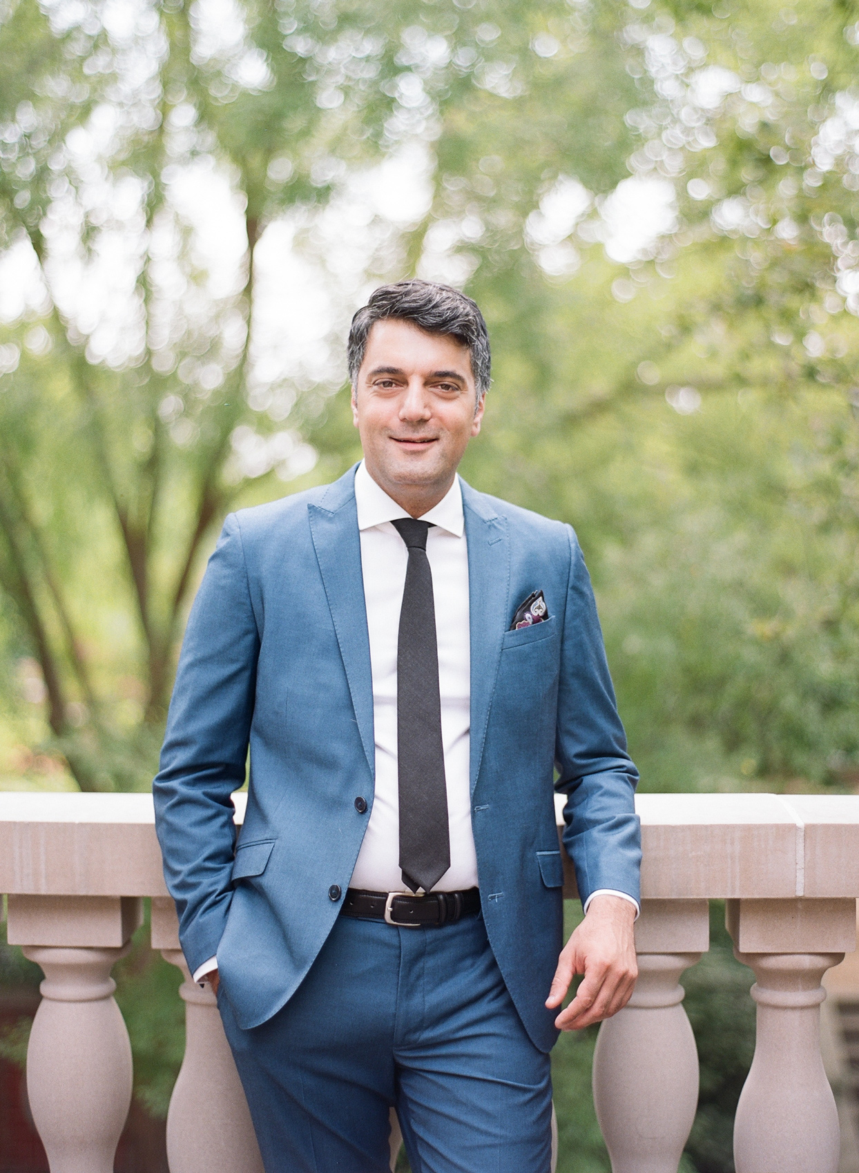 groom wearing blue suit leaning against railing