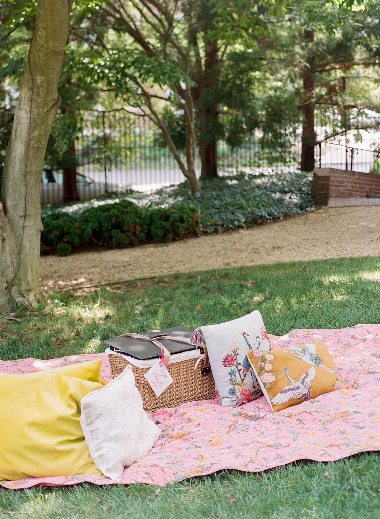 wedding picnic pink quilt and colorful pillows set up in garden