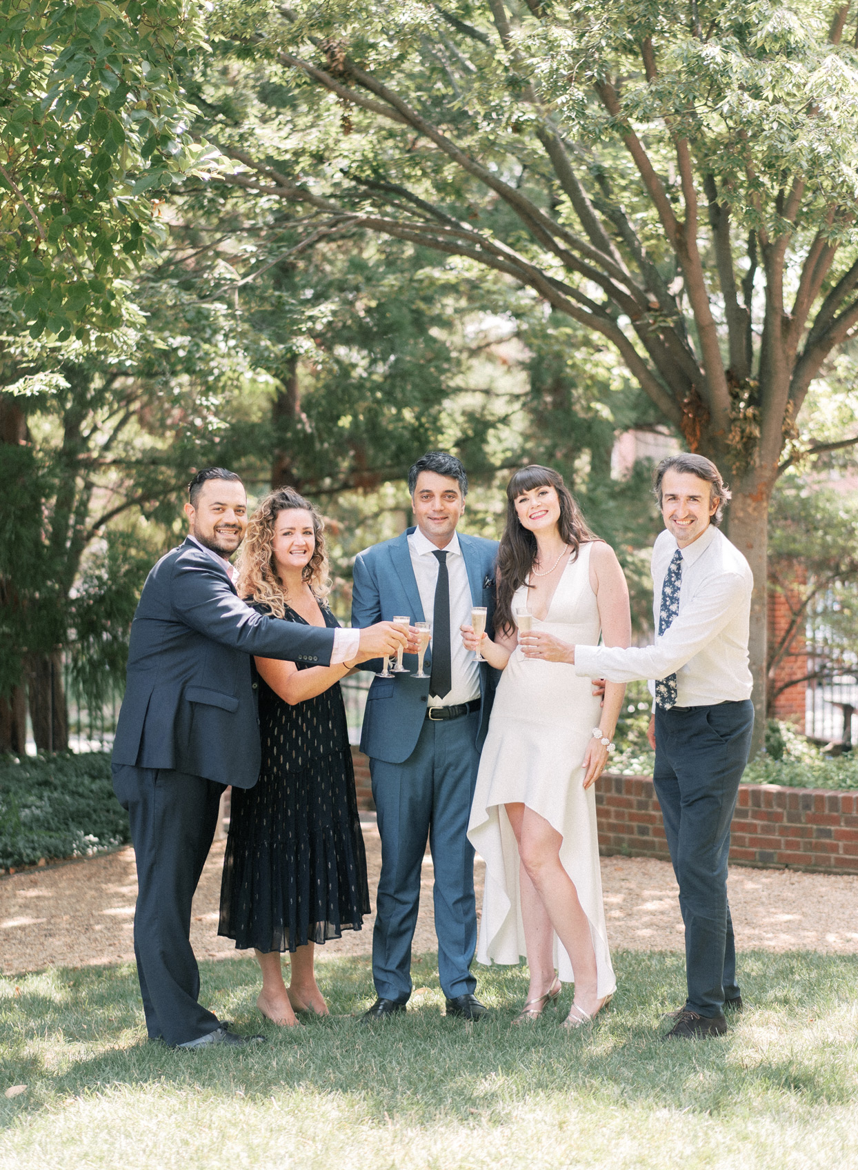 wedding attendees toasting bride and groom with champagne