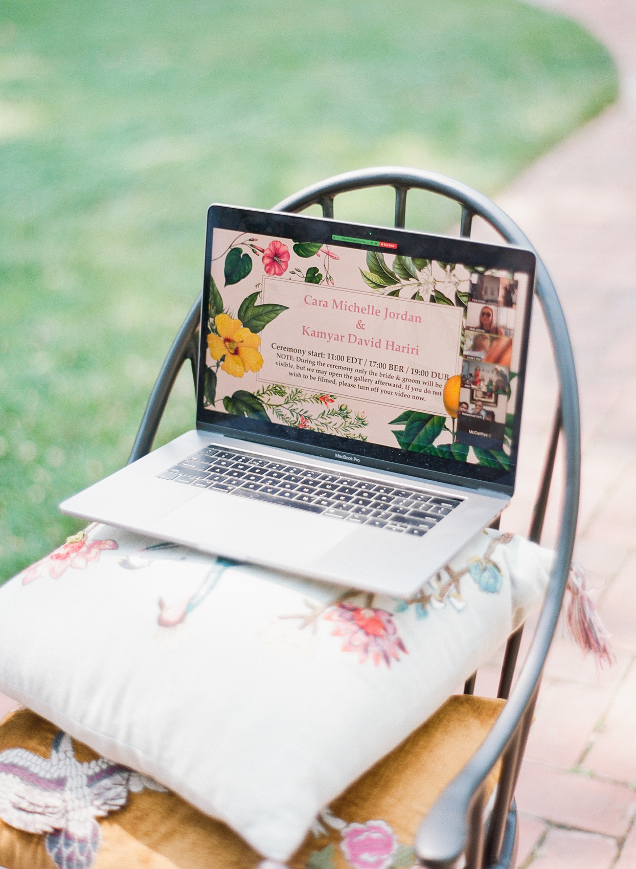 laptop propped up on decorative pillows streaming wedding ceremony