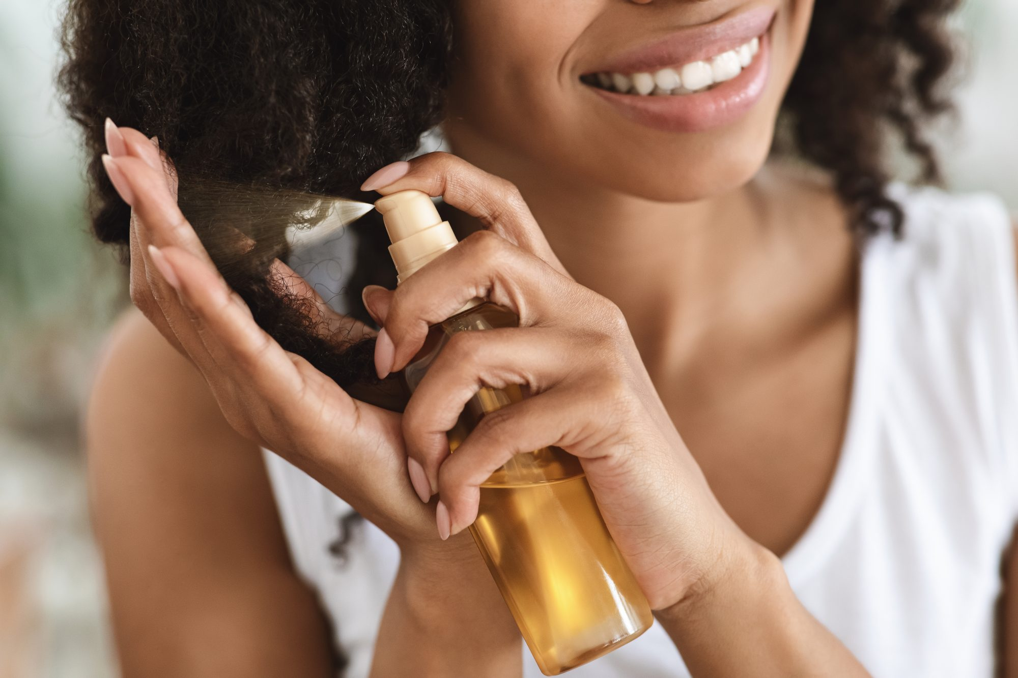 Smiling Woman Spraying Essential Oil On Curly Hair