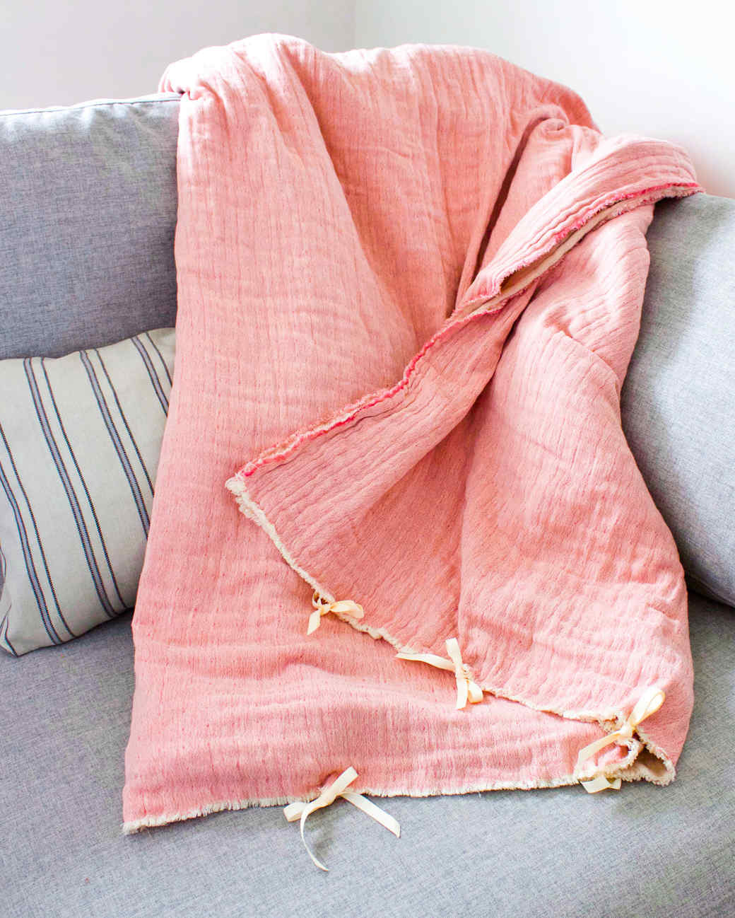 pink weighted blanket on gray couch