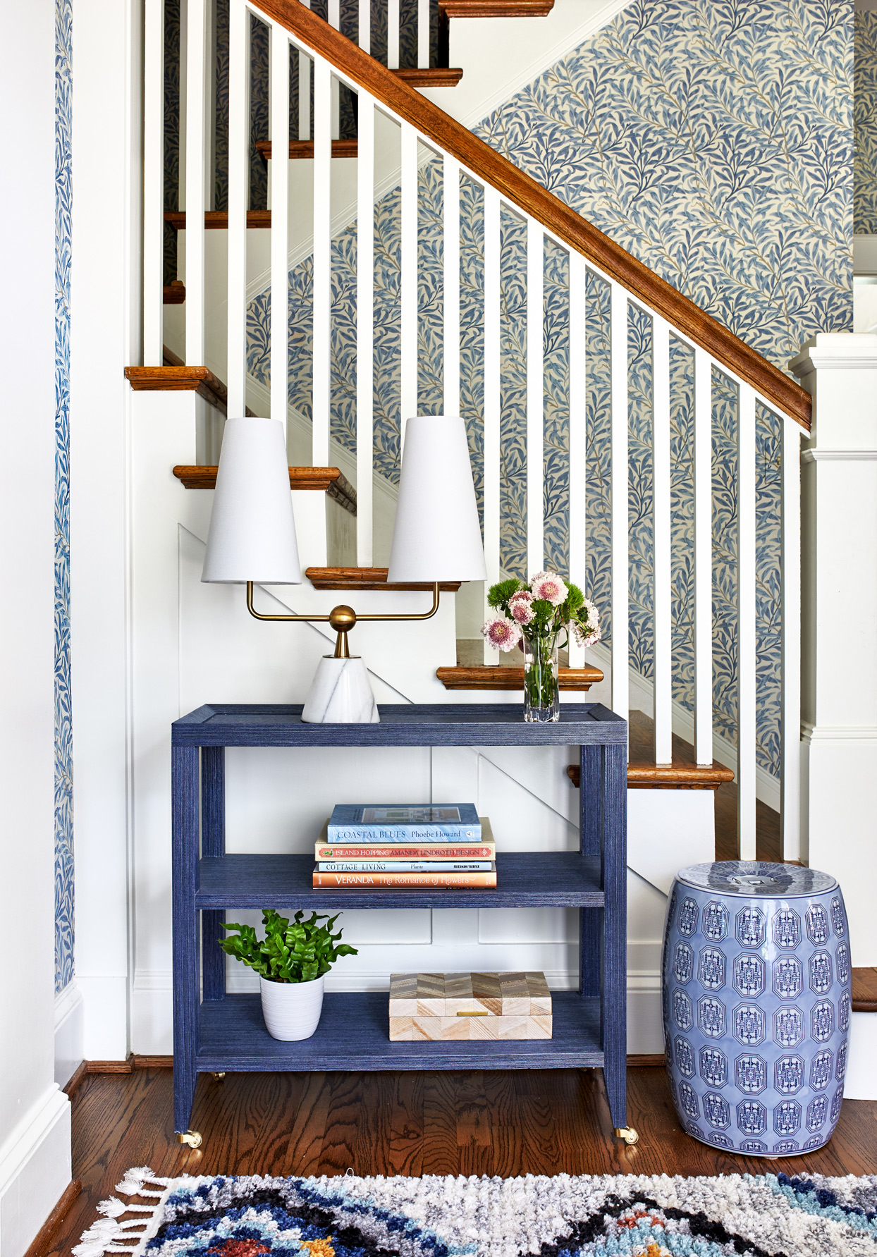 entryway staircase with blue botanical wallpaper