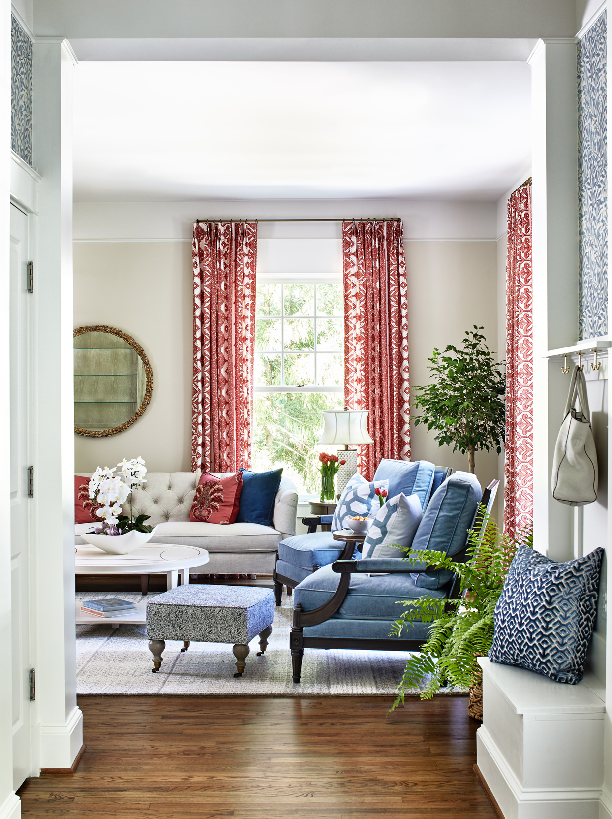 entryway overlooking neutral-colored living room with blue chairs and red accent pieces