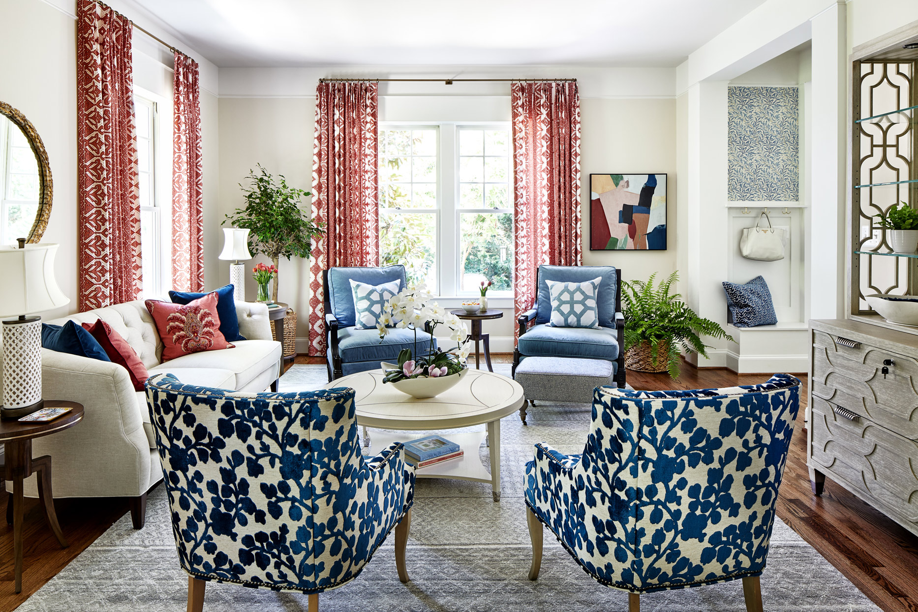 neutral-colored living room with blue chairs and red accent pieces