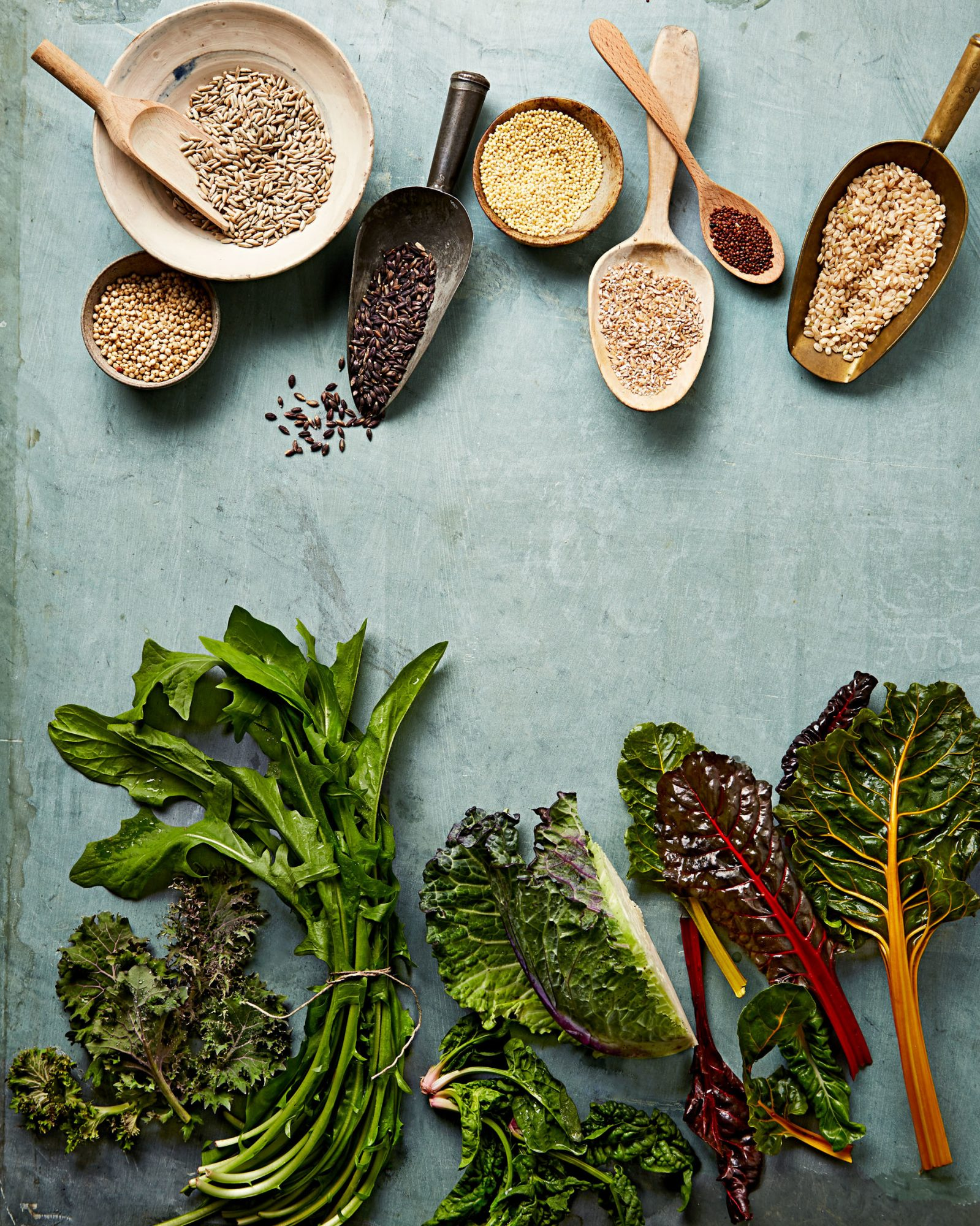 Whole grains including millet and quinoa, in scoops and raw leafy green vegetables, including spinach and dandelions, on a blue surface.