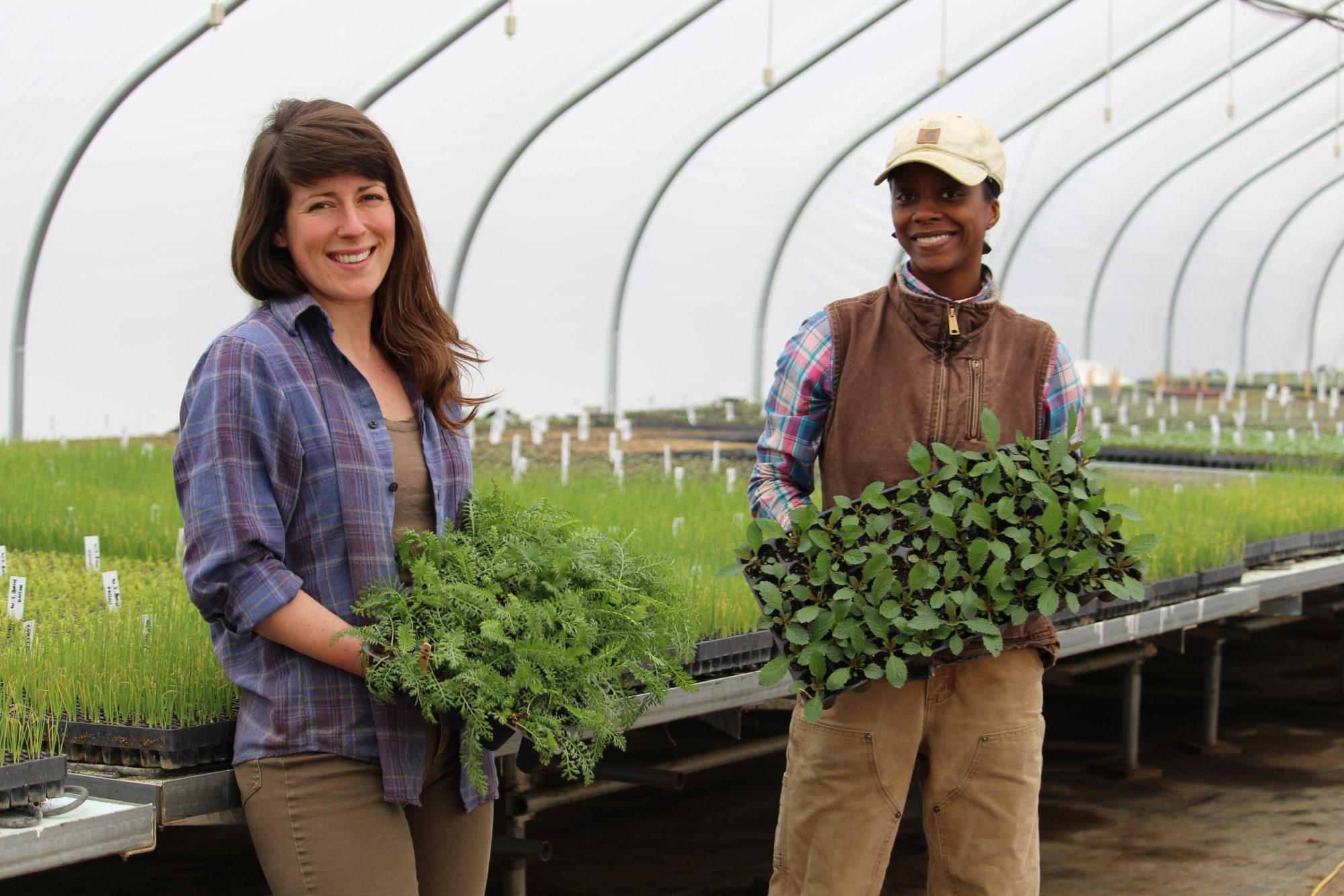 two women farmers holding trays of plants