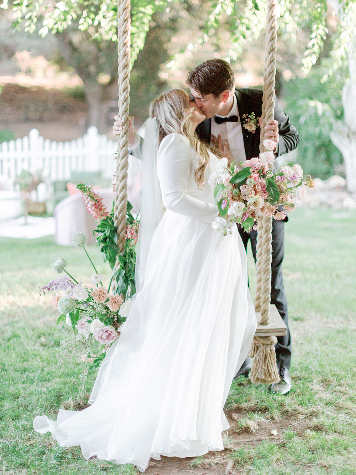 bride on wooden swing held up by ropes and floral accents kissing groom standing behind