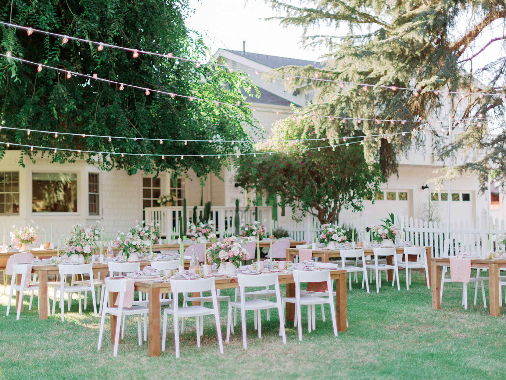 long wooden tables outdoors with white chairs and overhead string lights