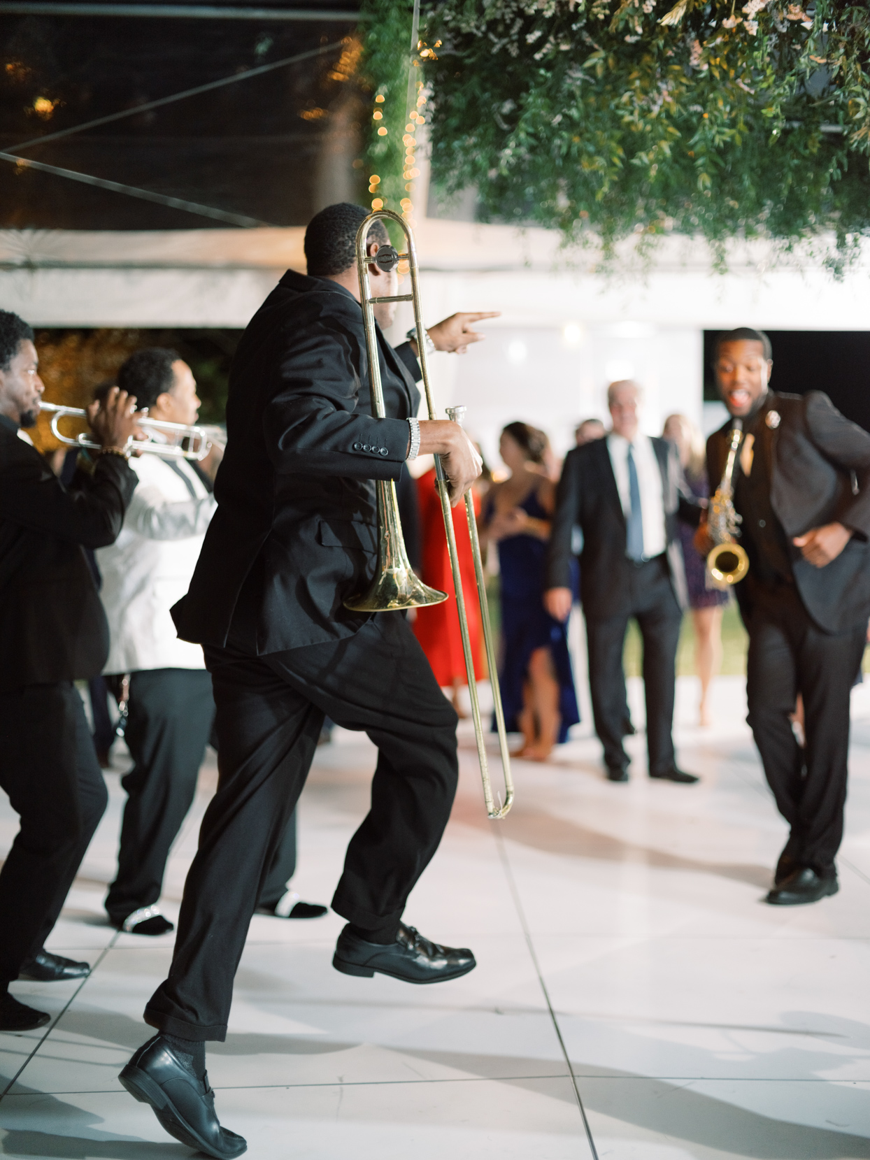 wedding musicians dancing with brass instruments at reception
