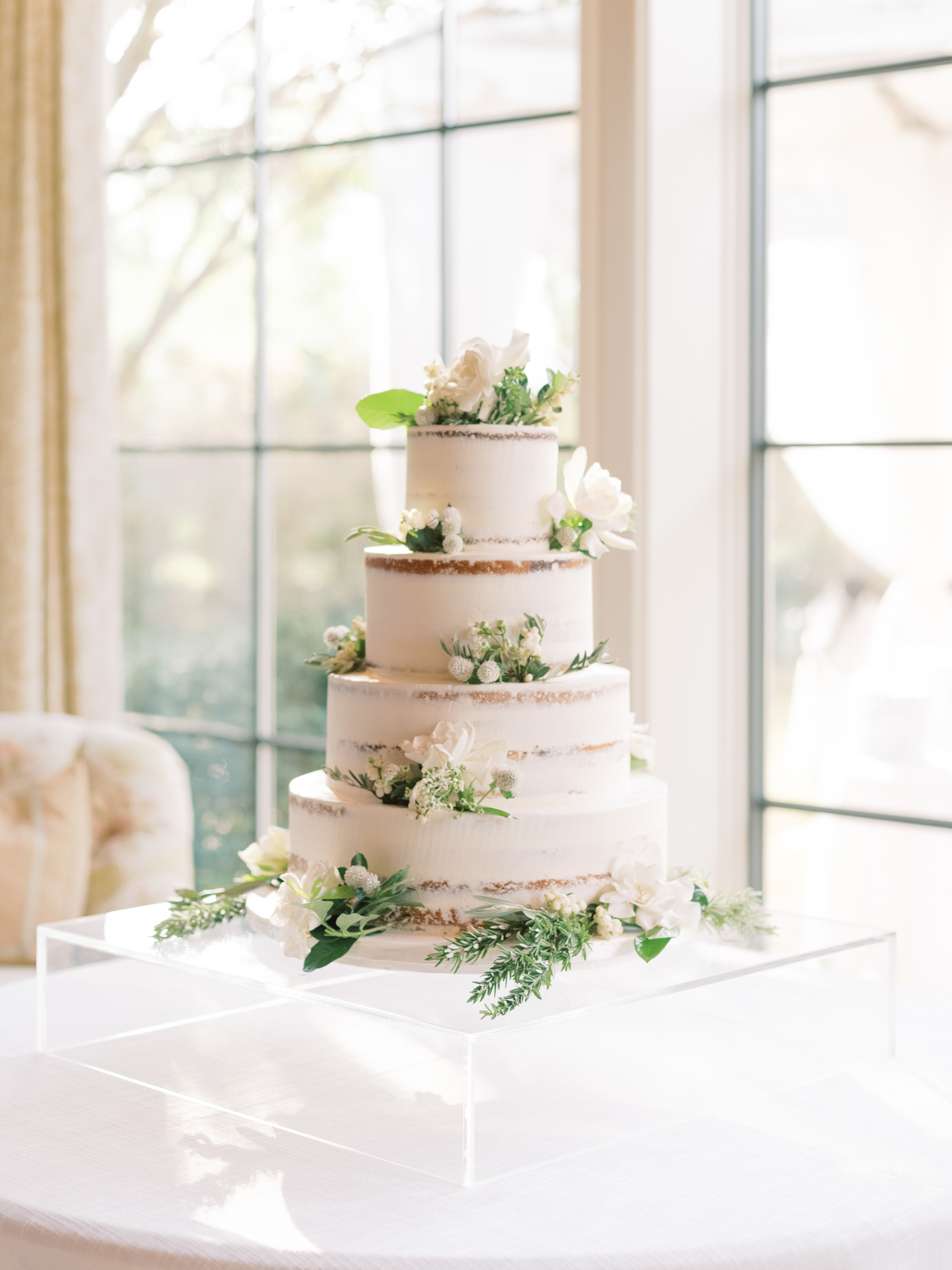 simple partially naked wedding cake with white flowers and greenery decor