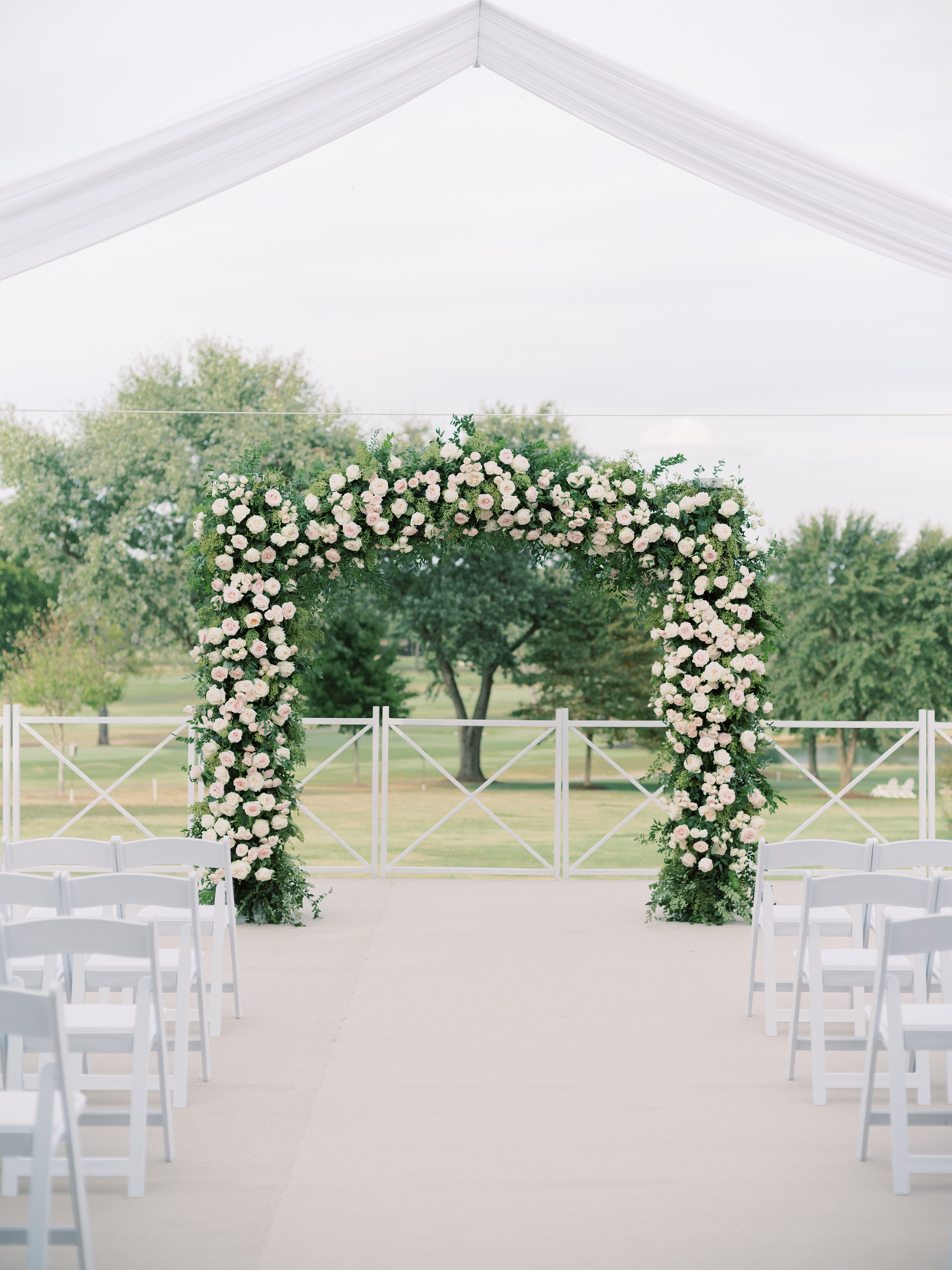 outdoor wedding ceremony location with pastel floral arch