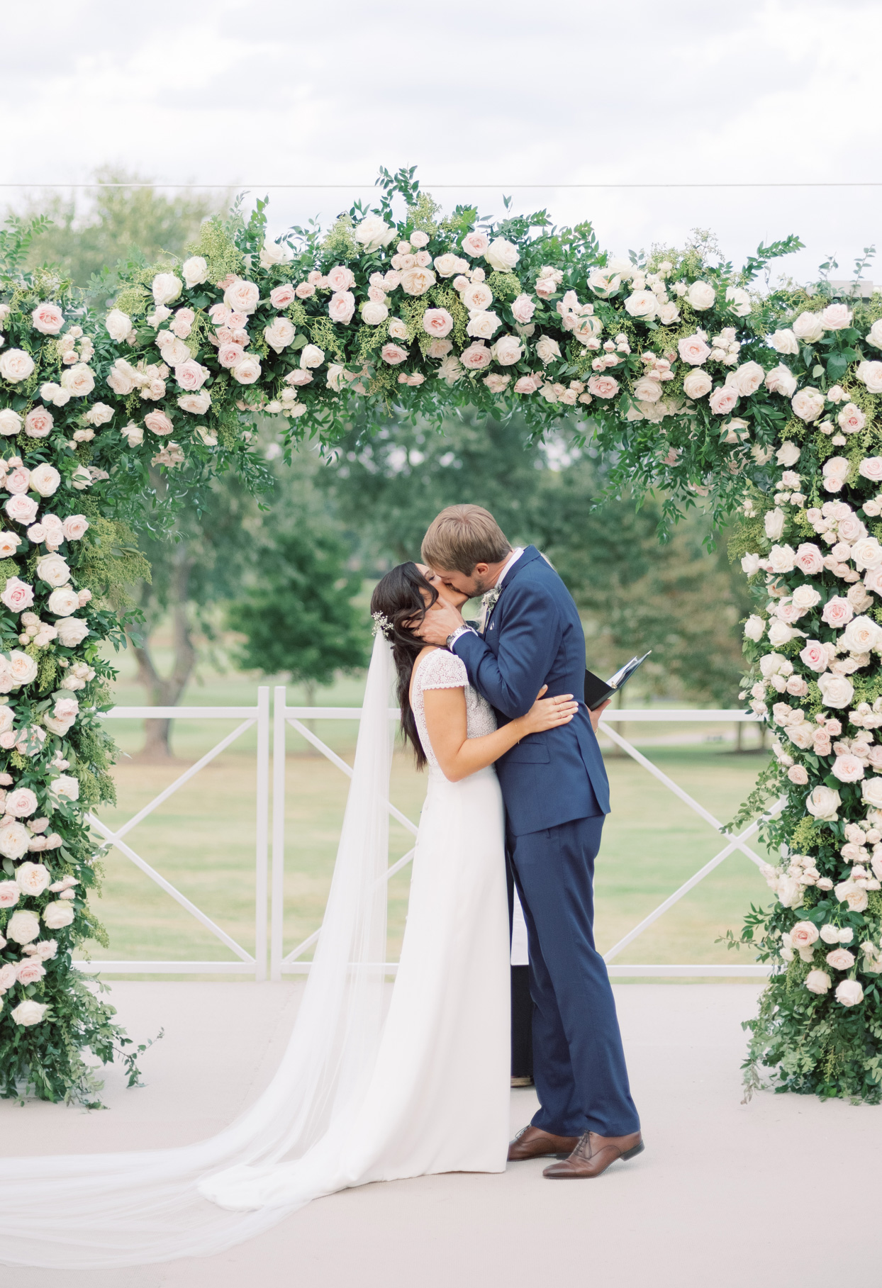 bride and groom kiss under floral arch during wedding ceremony