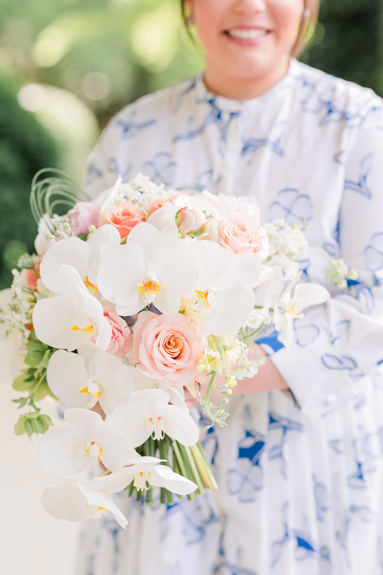 bride holding white and blush floral wedding bouquet