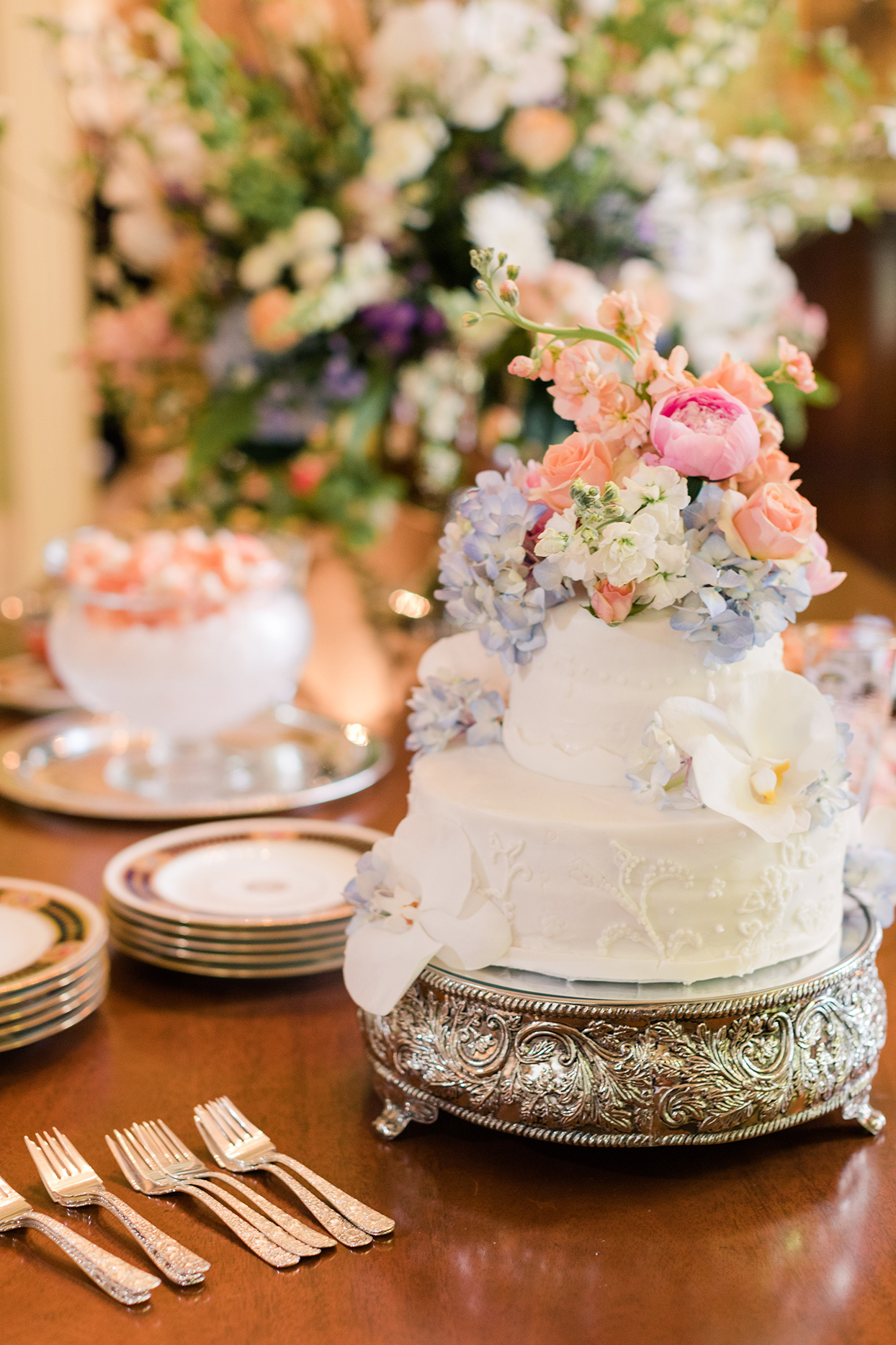 two tier white wedding cake with floral topper