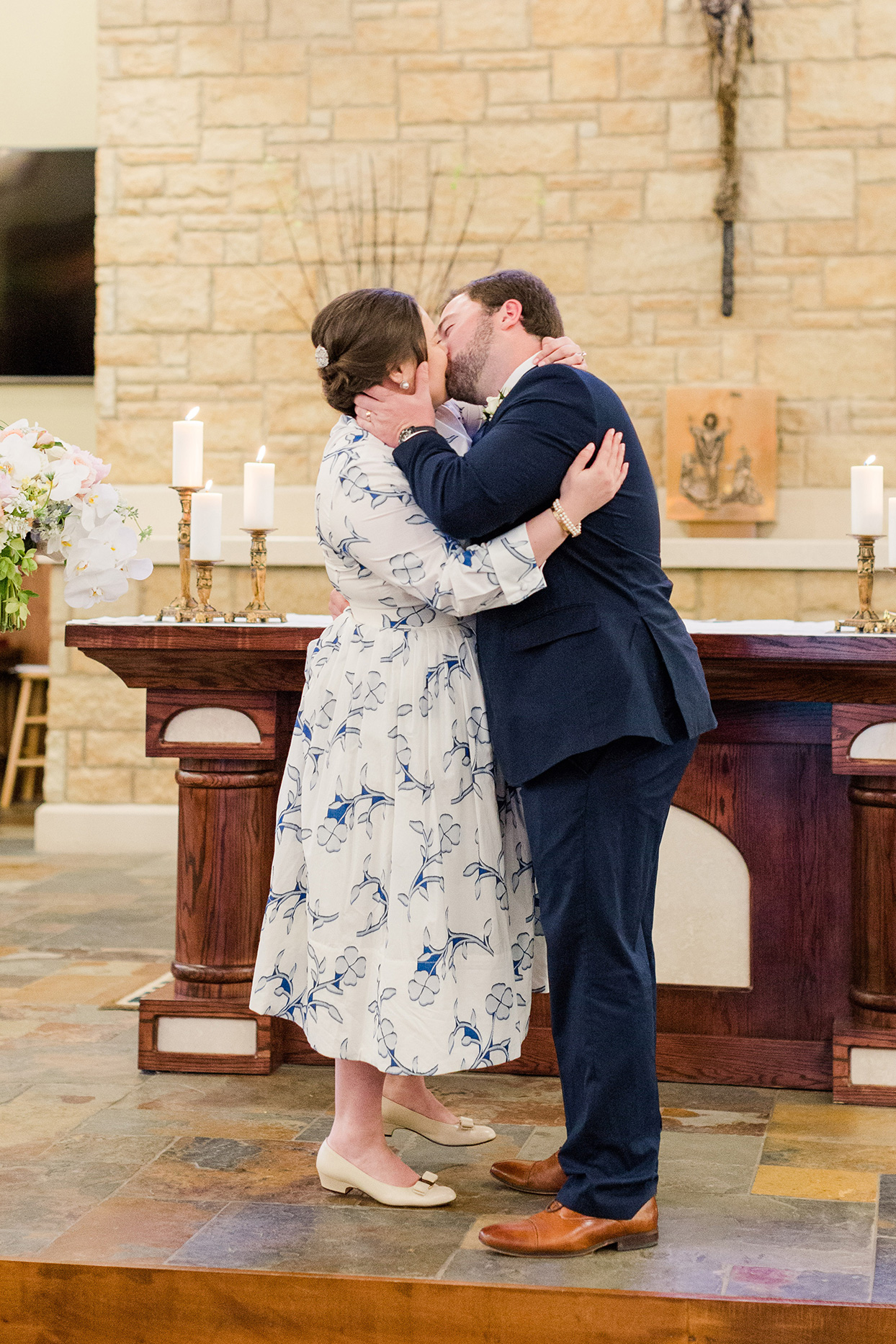 bride and groom kiss after wedding ceremony in church
