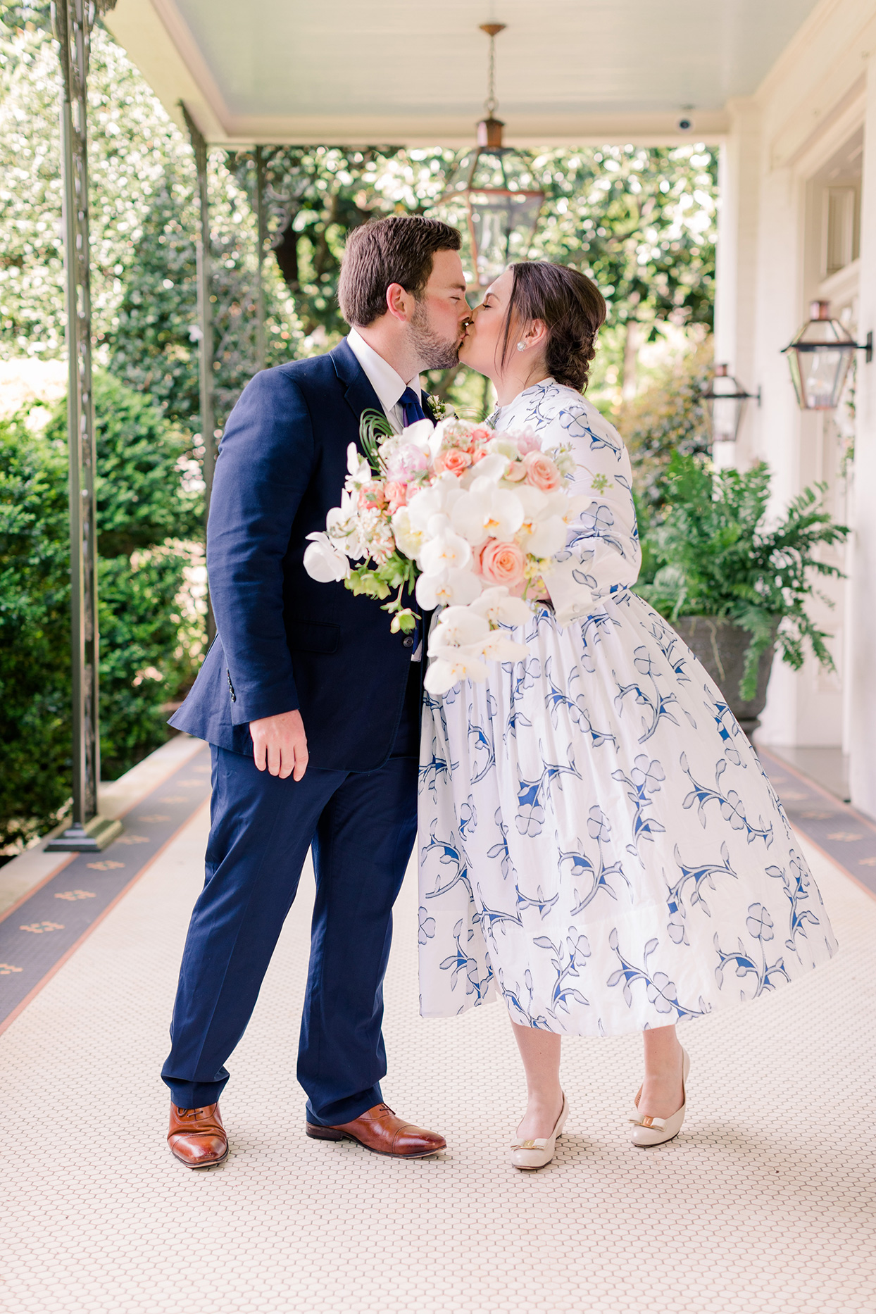 bride and groom kiss outside home