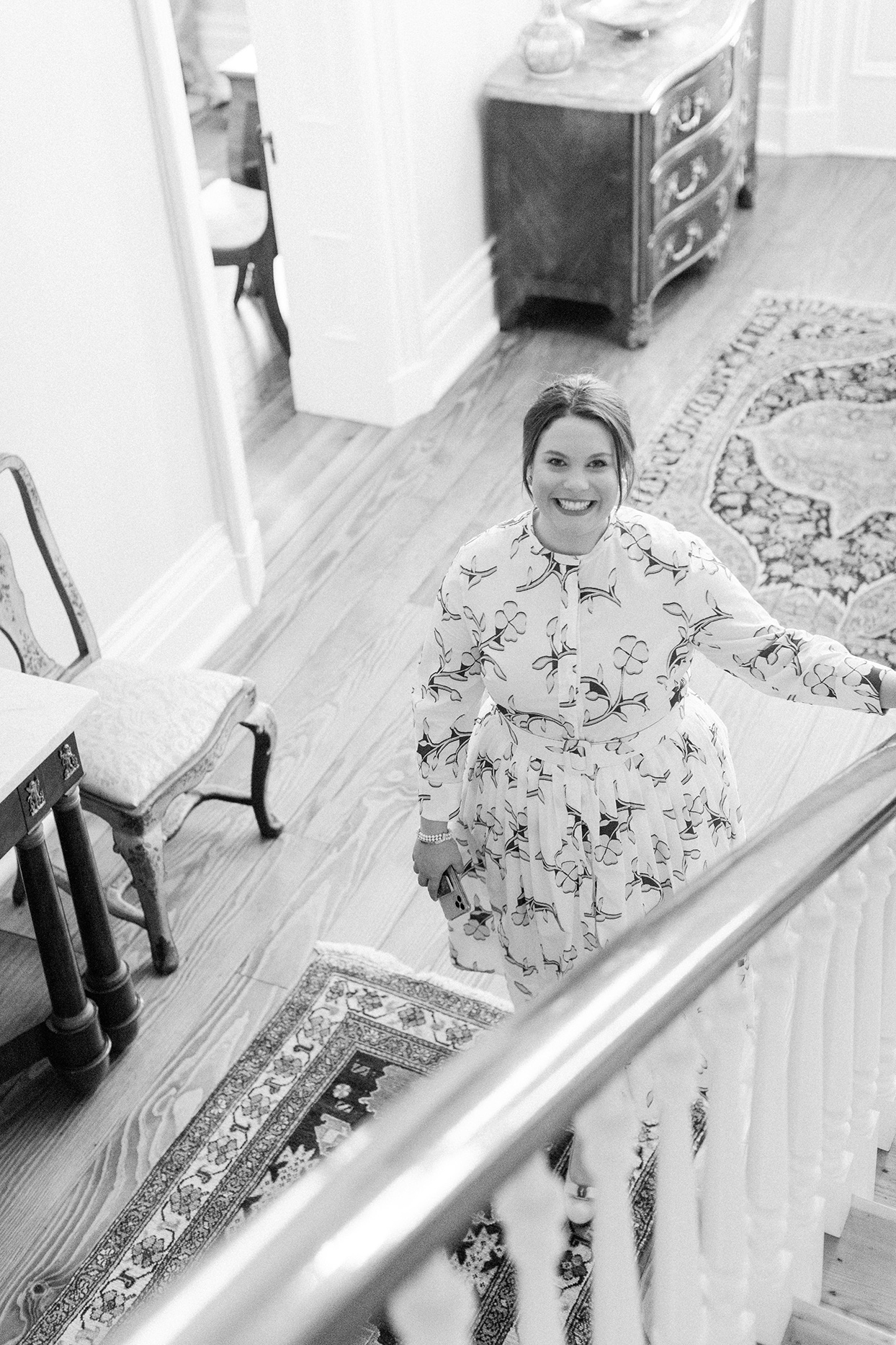bride smiling at bottom of staircase wearing white cocktail dress with blue floral pattern