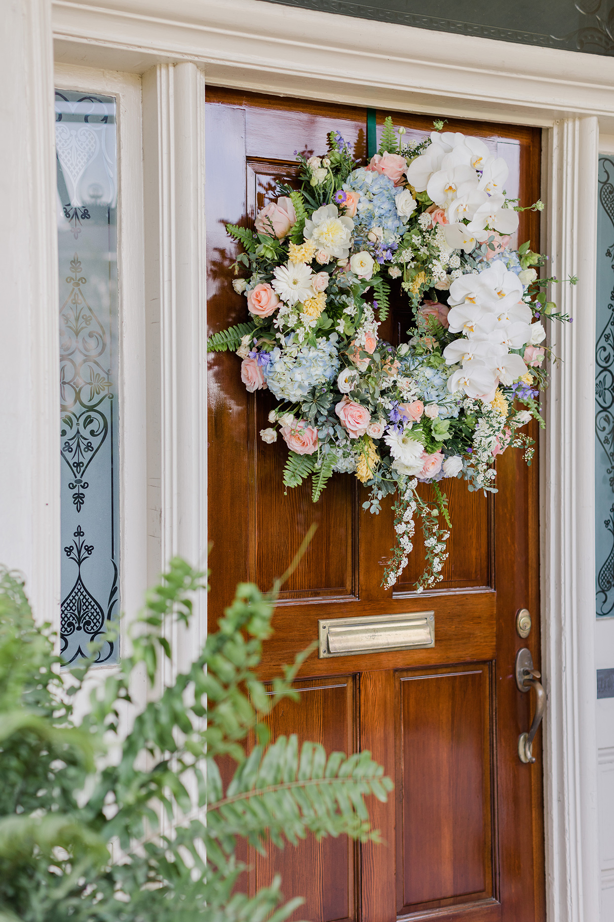 large various colored floral wedding wreath hanging on wooden front door