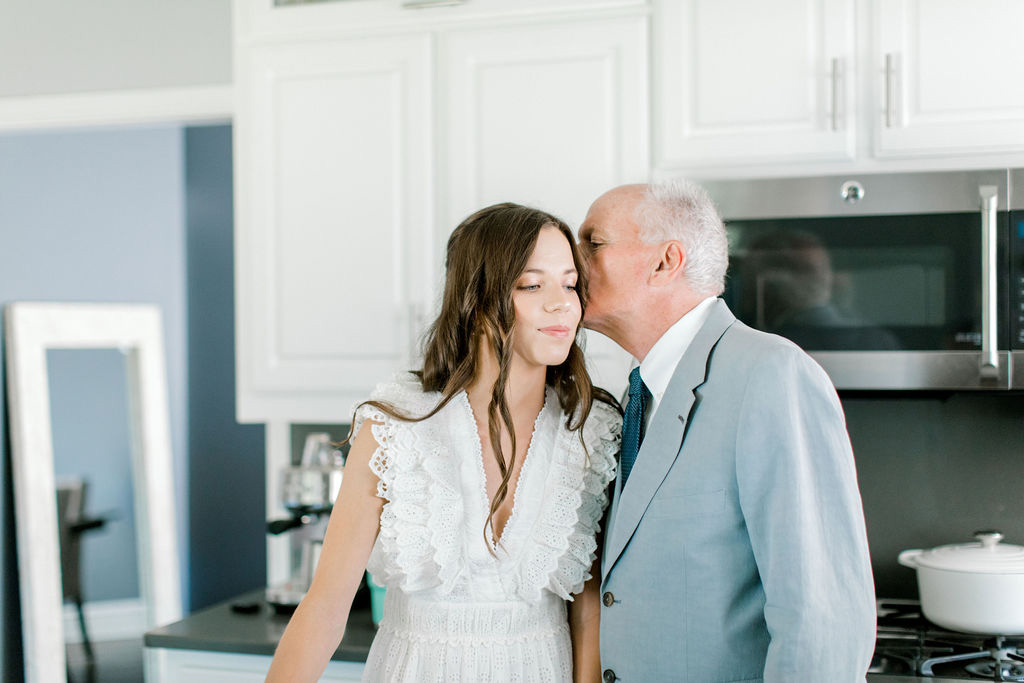 father of the bride kissing bride on forehead in the kitchen